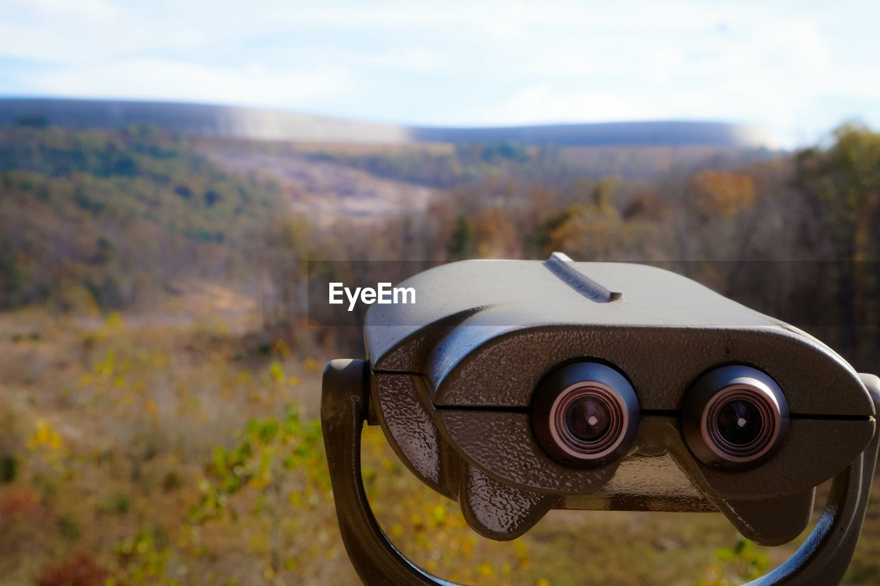 coin-operated binoculars, focus on foreground, no people, day, field, close-up, landscape, outdoors, nature, mountain, sky