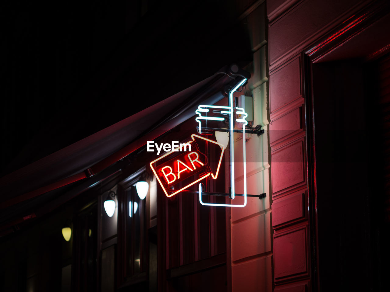 Low Angle View Of Illuminated Bar Sign At Night