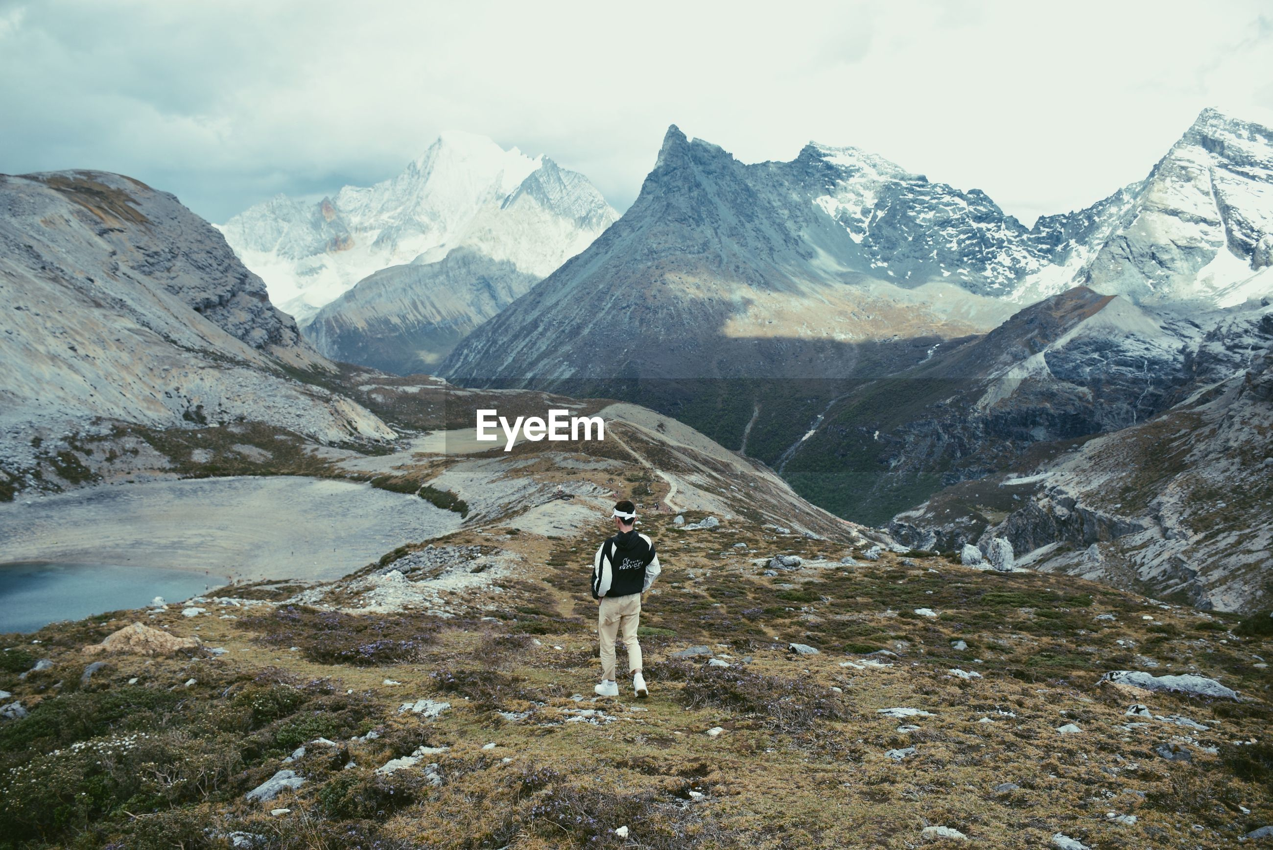 FULL LENGTH REAR VIEW OF MAN STANDING ON MOUNTAIN