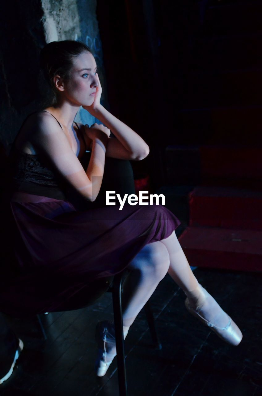 Ballet dancer sitting on chair in studio