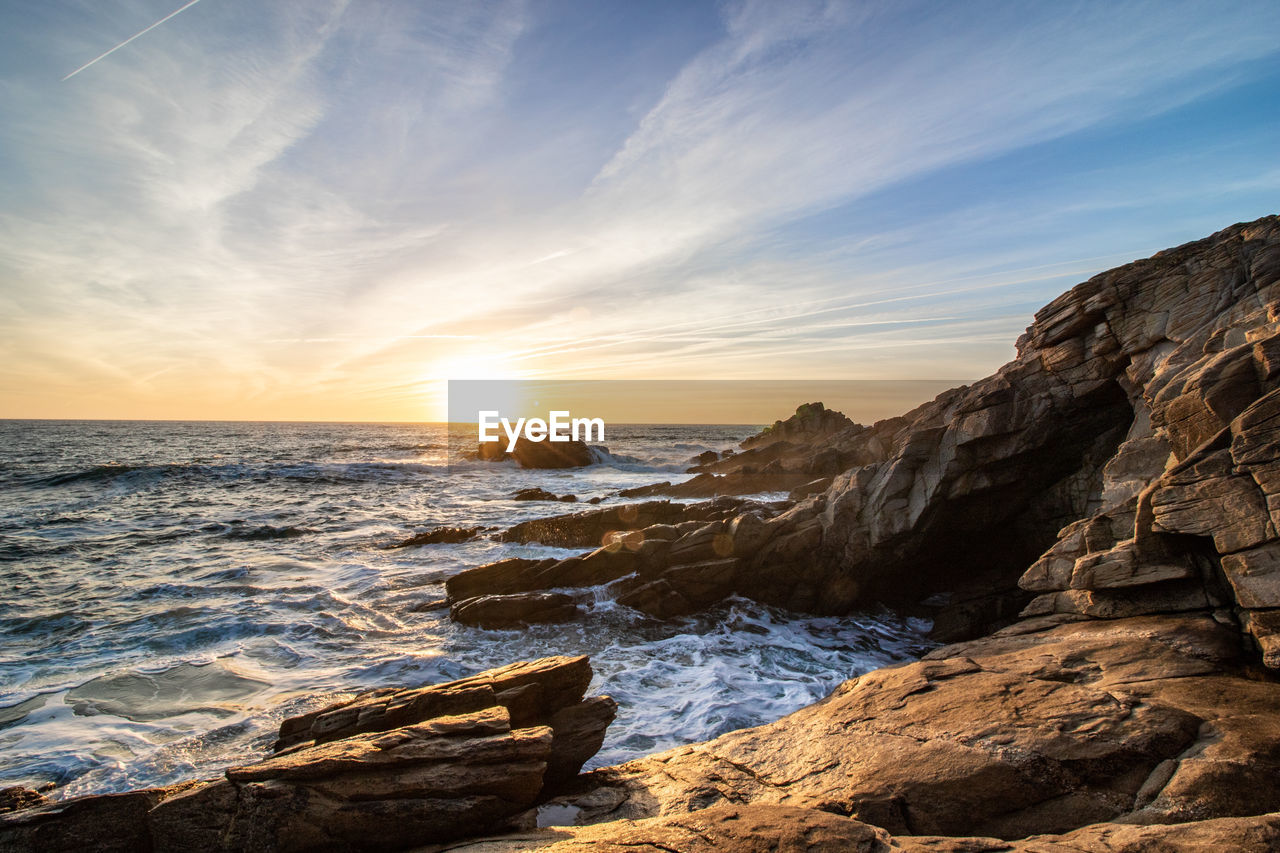 SCENIC VIEW OF ROCKS ON SEA AGAINST SKY DURING SUNSET