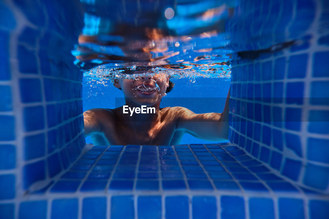 REFLECTION OF MAN SWIMMING IN POOL