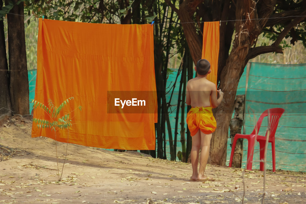 real people, one person, full length, rear view, clothesline, day, shirtless, textile, lifestyles, leisure activity, outdoors, tree, standing, drying, hanging, people