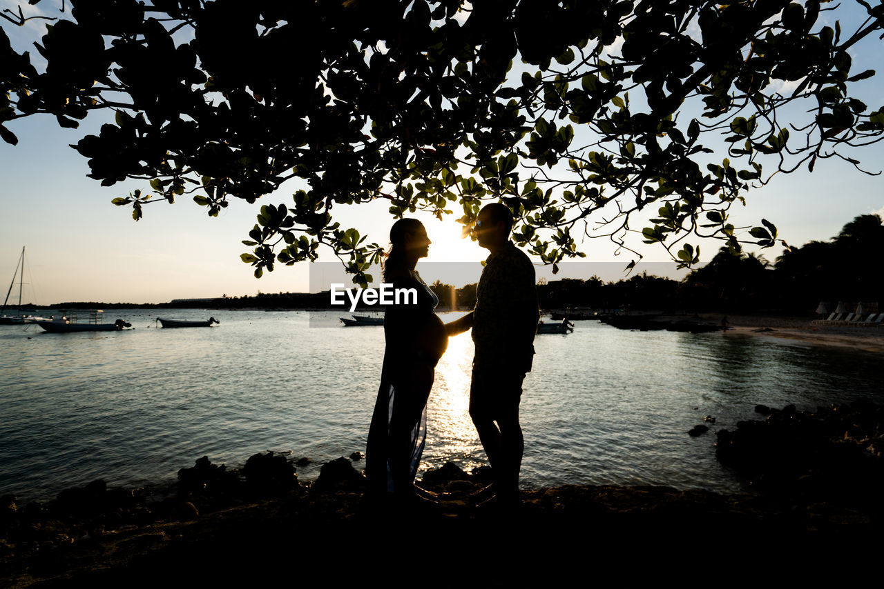 water, togetherness, tree, two people, sky, nature, lake, couple - relationship, standing, plant, real people, bonding, women, emotion, adult, silhouette, love, beauty in nature, positive emotion, outdoors