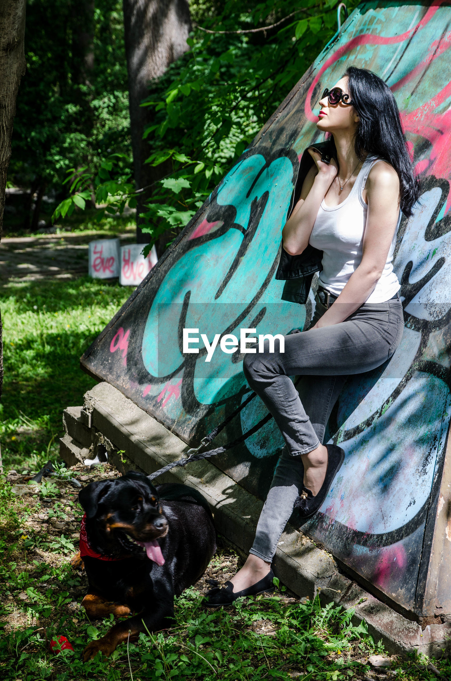 young adult, one person, dog, mammal, full length, domestic animals, canine, casual clothing, domestic, real people, one animal, lifestyles, pets, young women, day, graffiti, sitting, outdoors, pet owner, hairstyle
