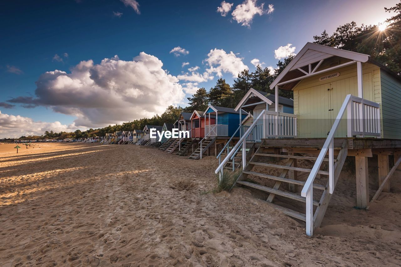Huts By Sandy Beach Against Cloudy Sky