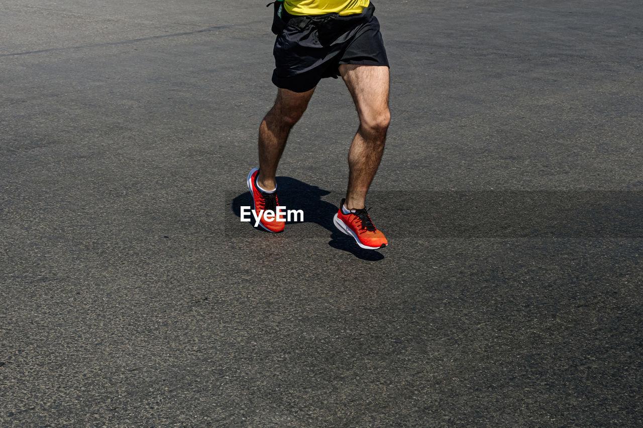 Legs runner man in orange shoes running on dark road