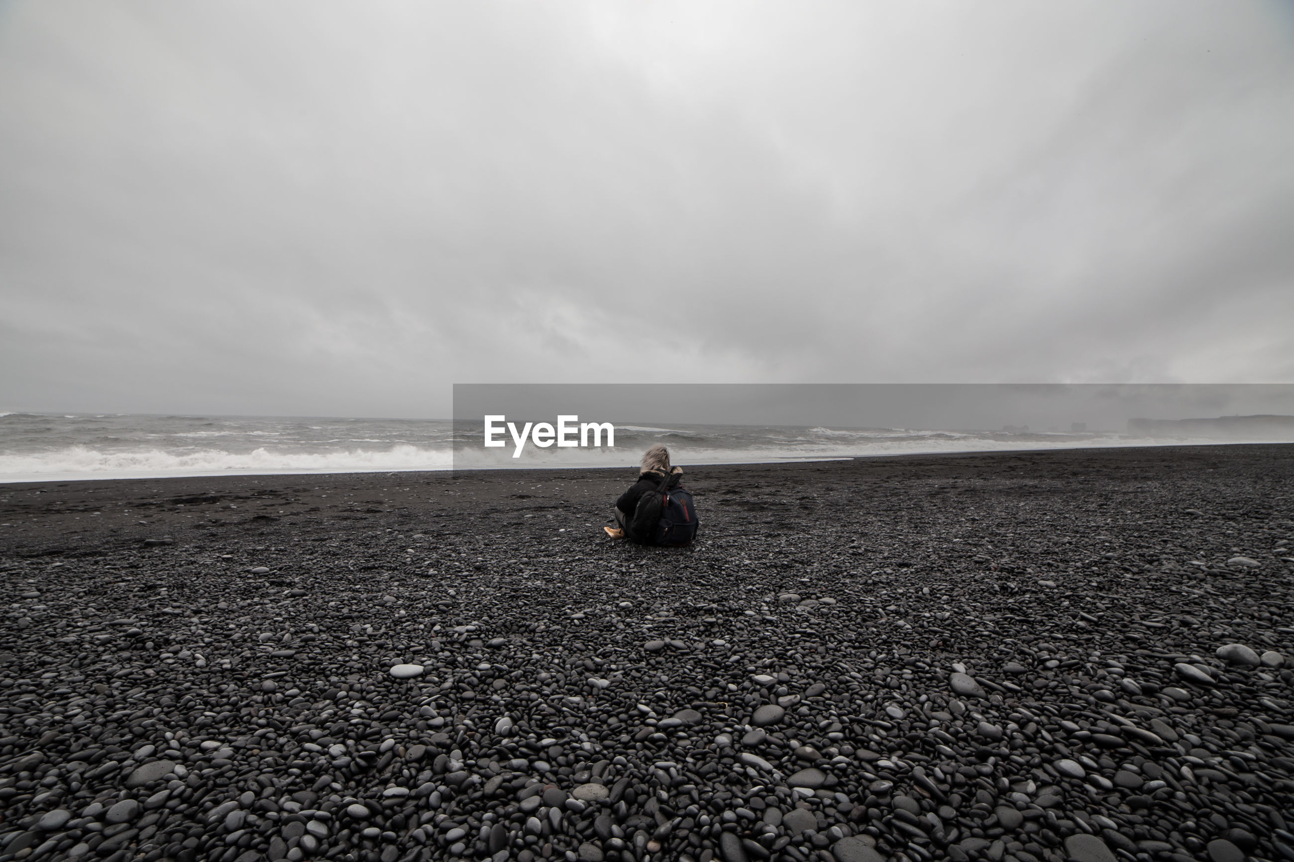 Rear view of woman sitting on pebbles at beach against sky