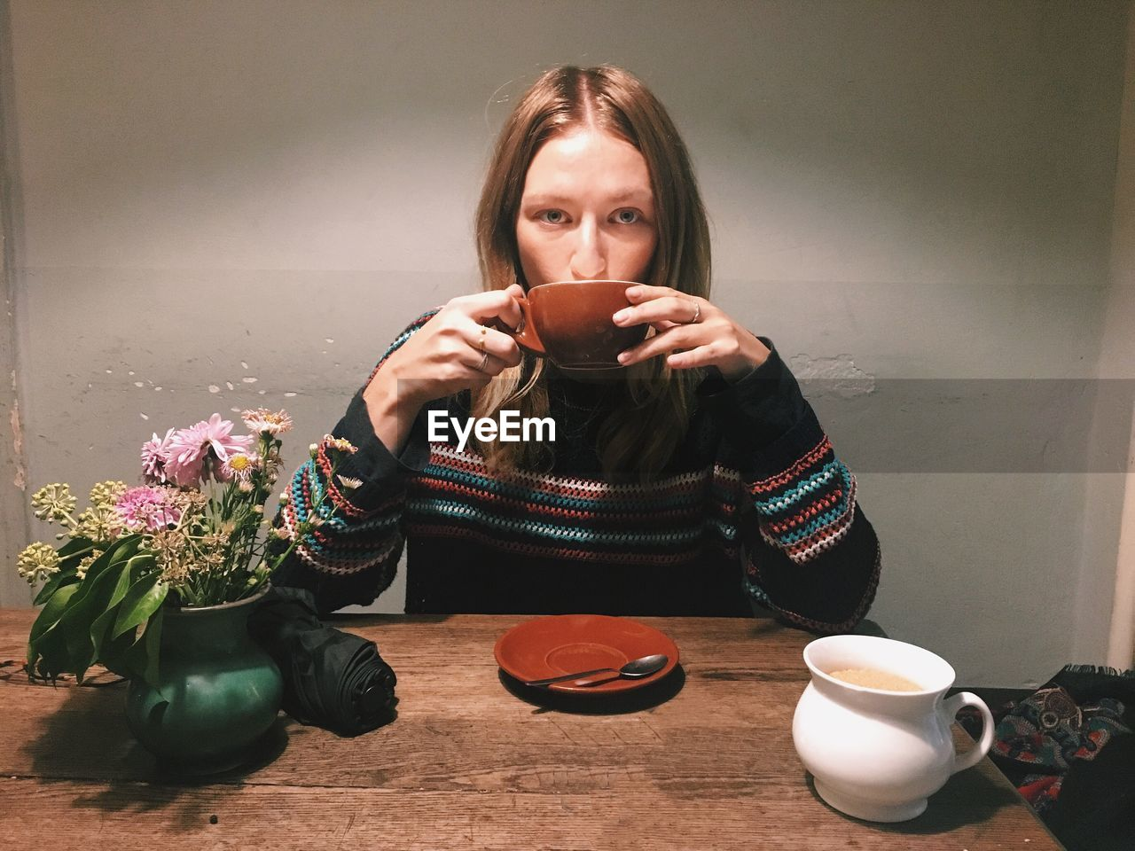Portrait Of Young Woman Drinking Coffee At Table In Cafe