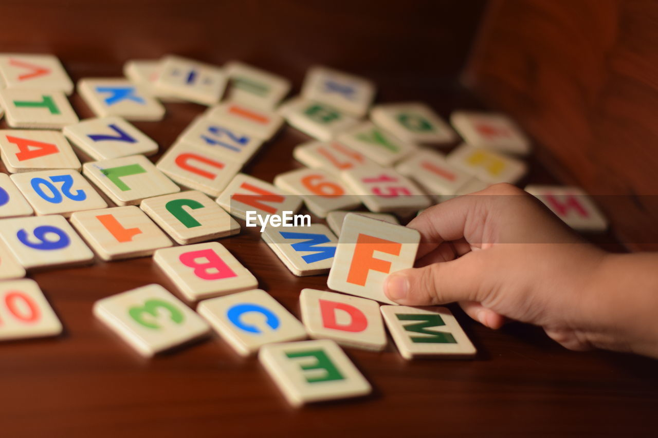 Cropped Image Of Child Holding Toy Blocks On Table