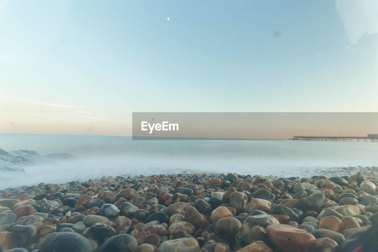 sky, sea, water, horizon over water, horizon, scenics - nature, rock, beach, solid, beauty in nature, stone, nature, pebble, tranquil scene, land, tranquility, stone - object, idyllic, rock - object, surface level