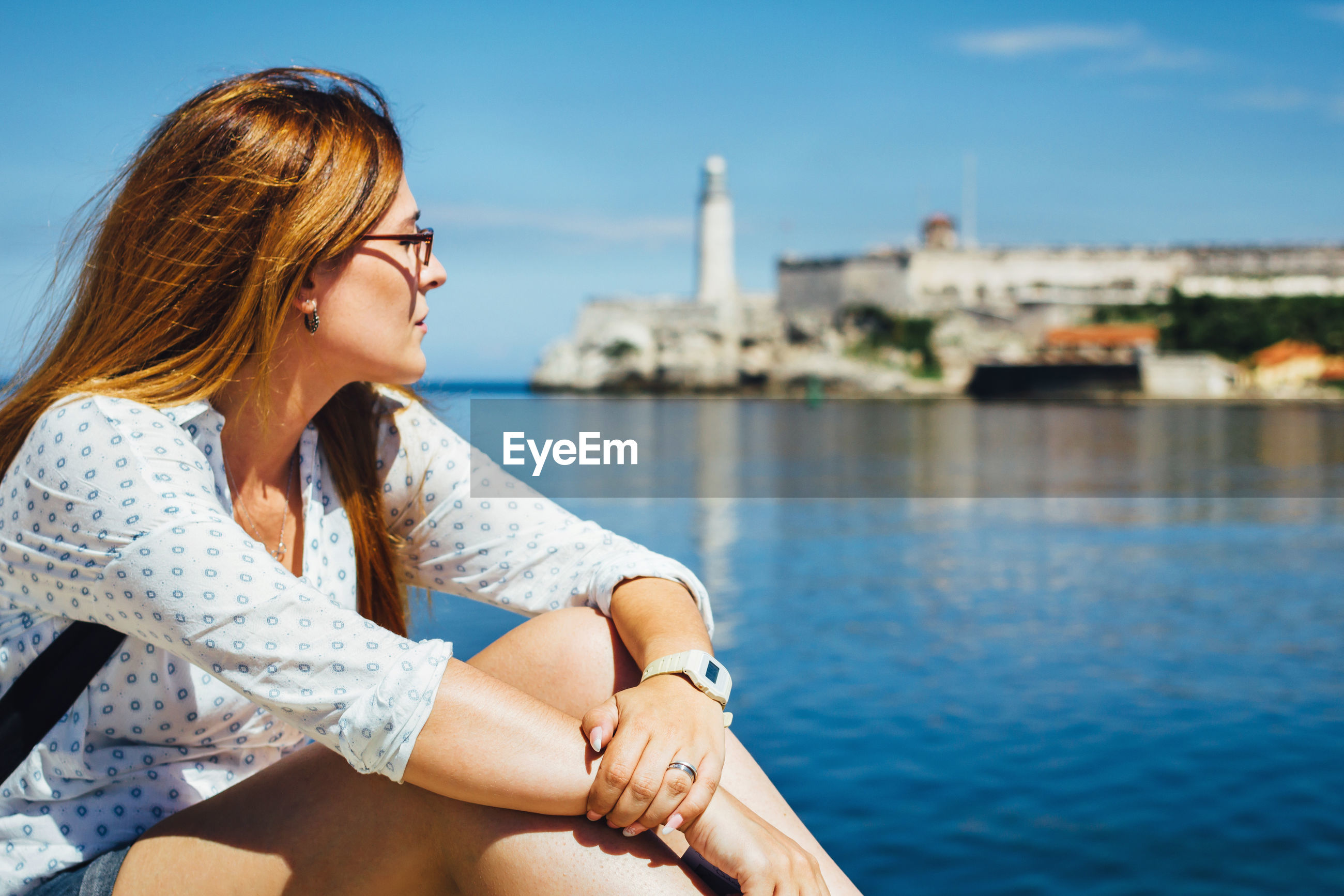 Young woman looking away while sitting by river against blue sky during sunny day
