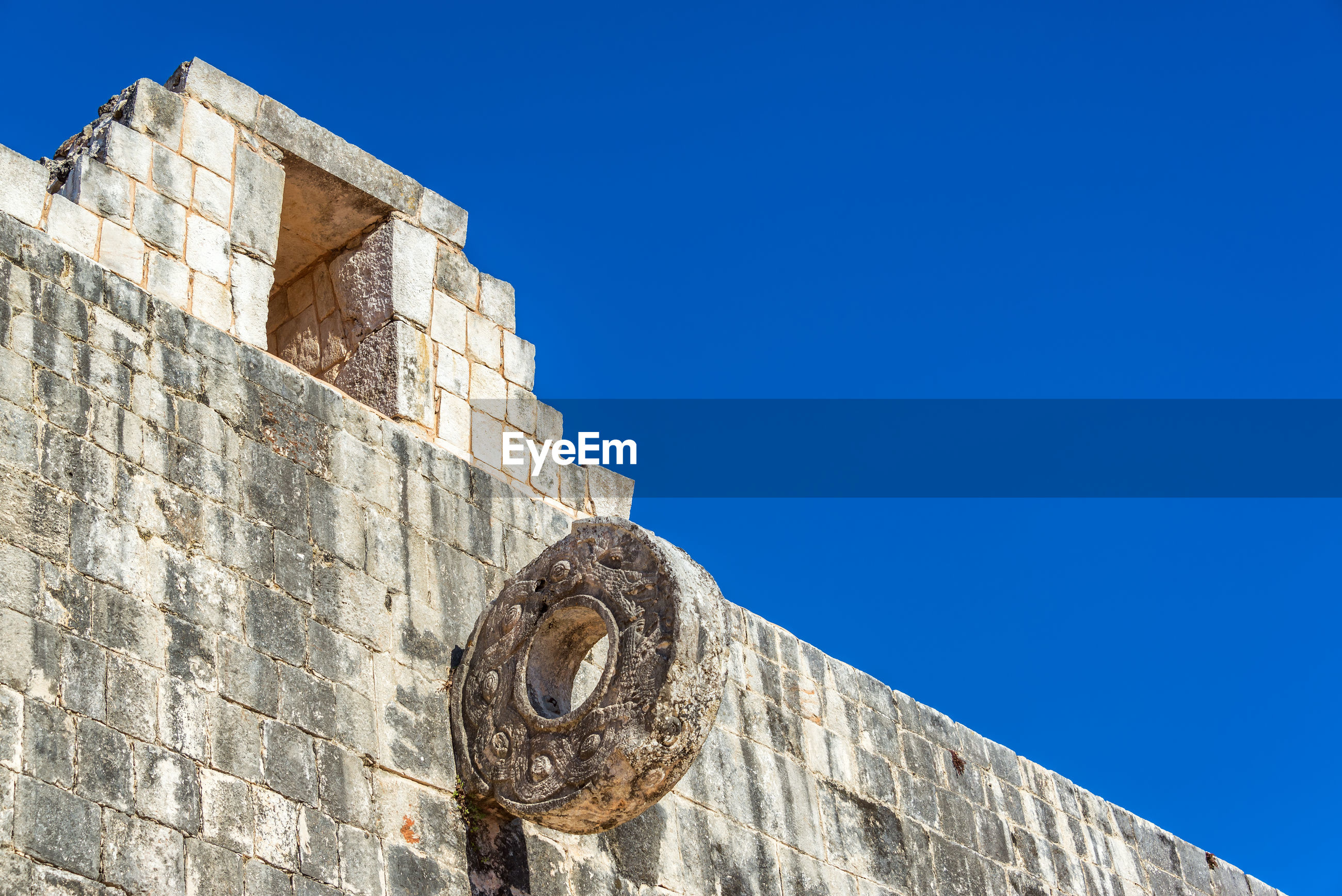 Low angle view of kukulkan pyramid against clear blue sky during sunny day