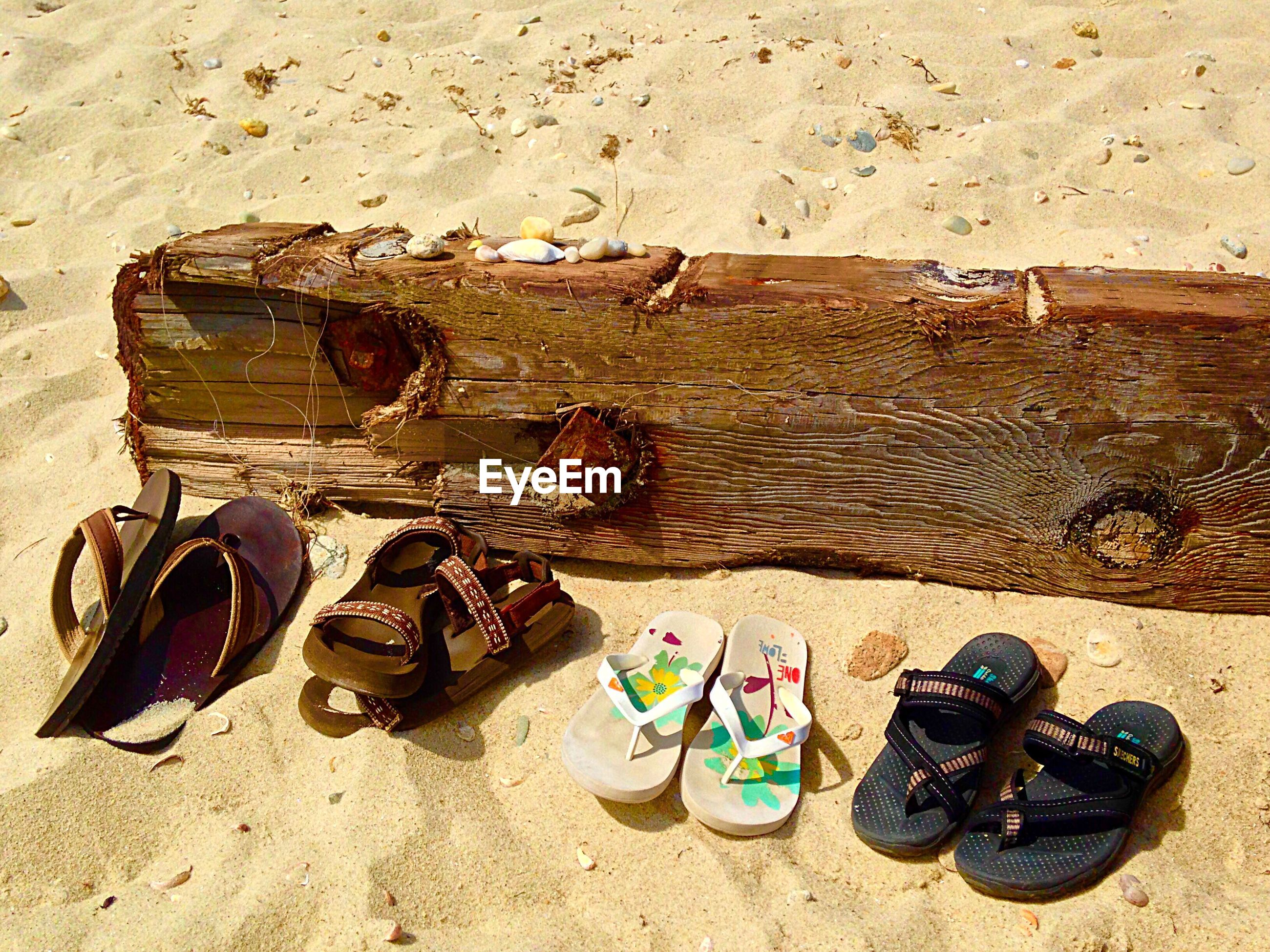 Pair of footwear by wooden plank at beach