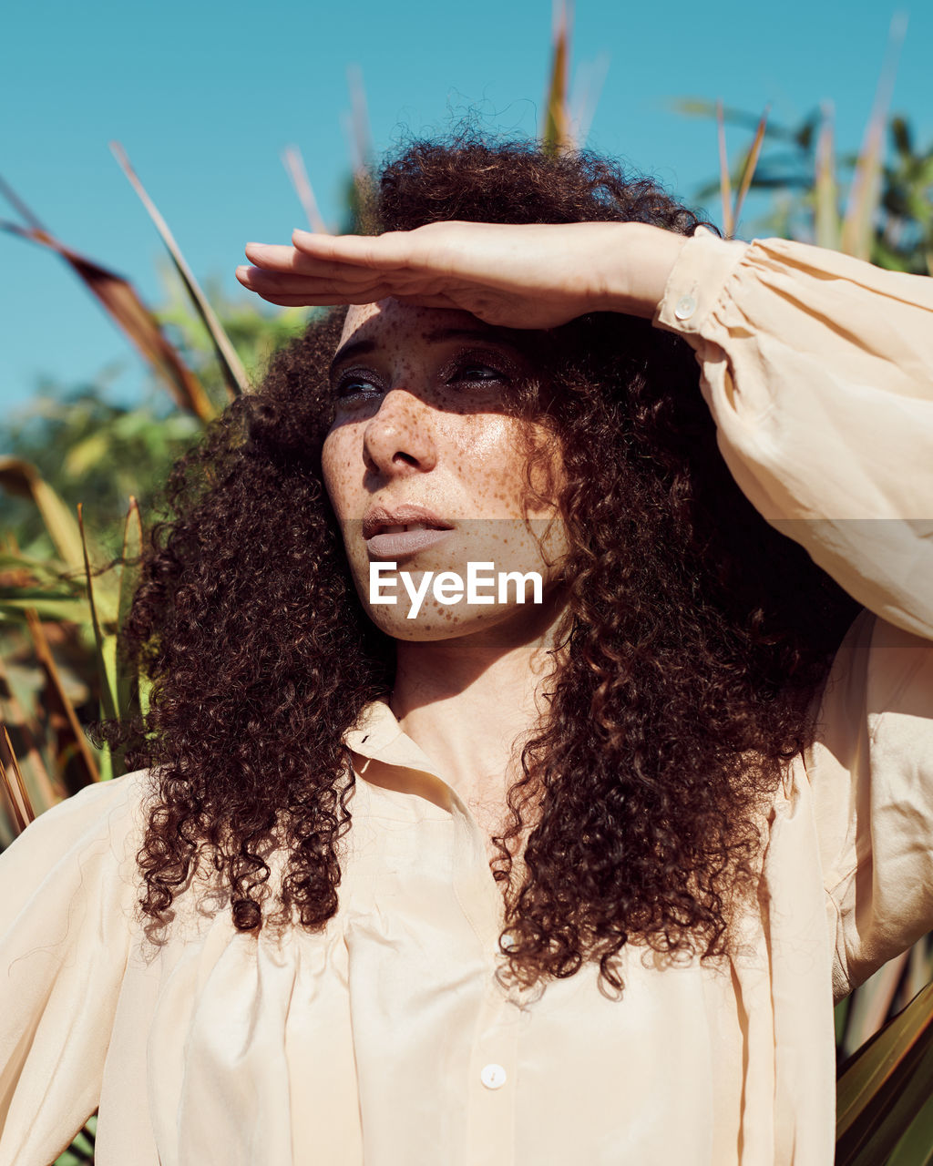 Close-up of woman shielding eyes against plants