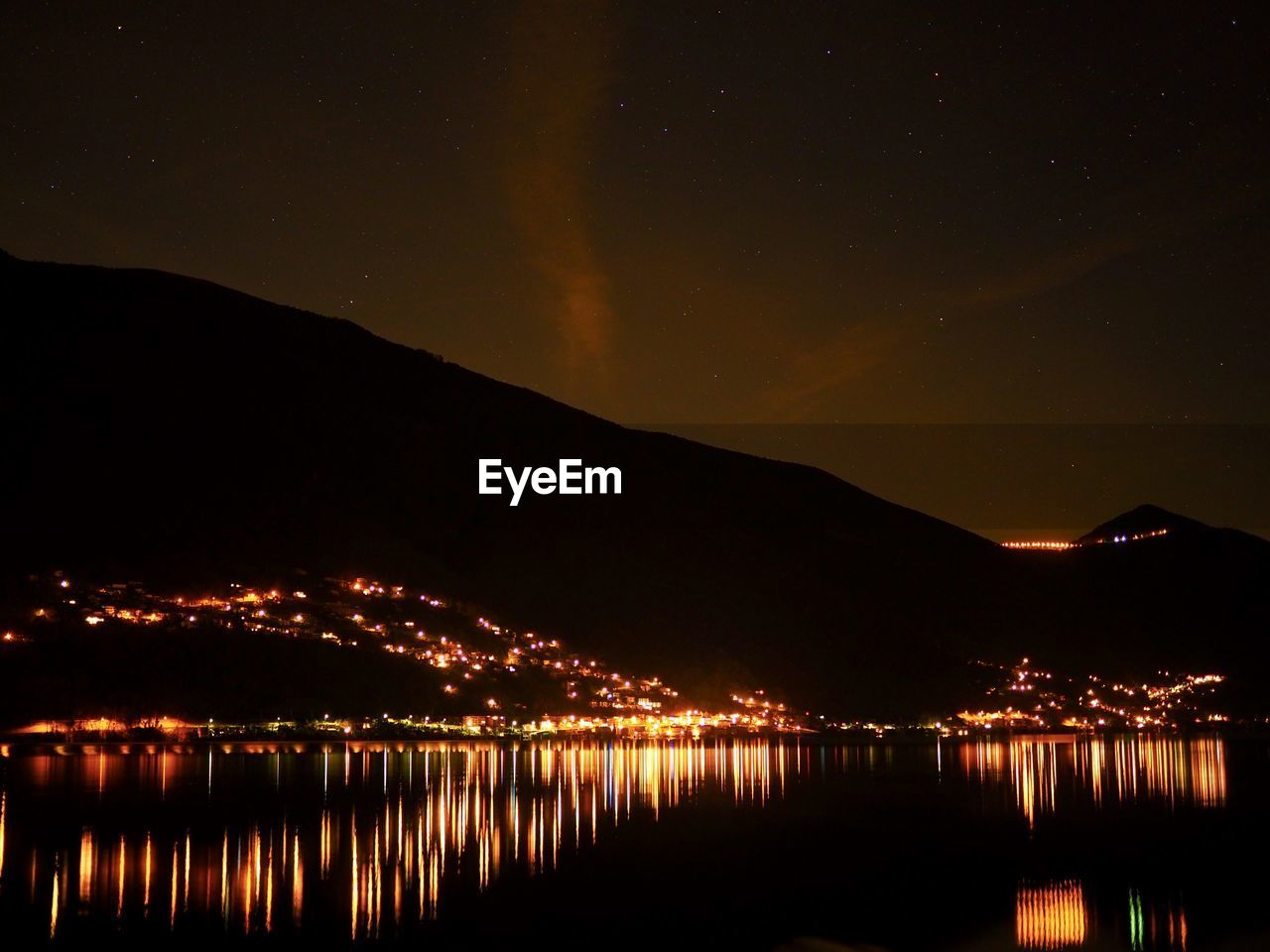 RIVER BY ILLUMINATED MOUNTAIN AGAINST SKY AT NIGHT