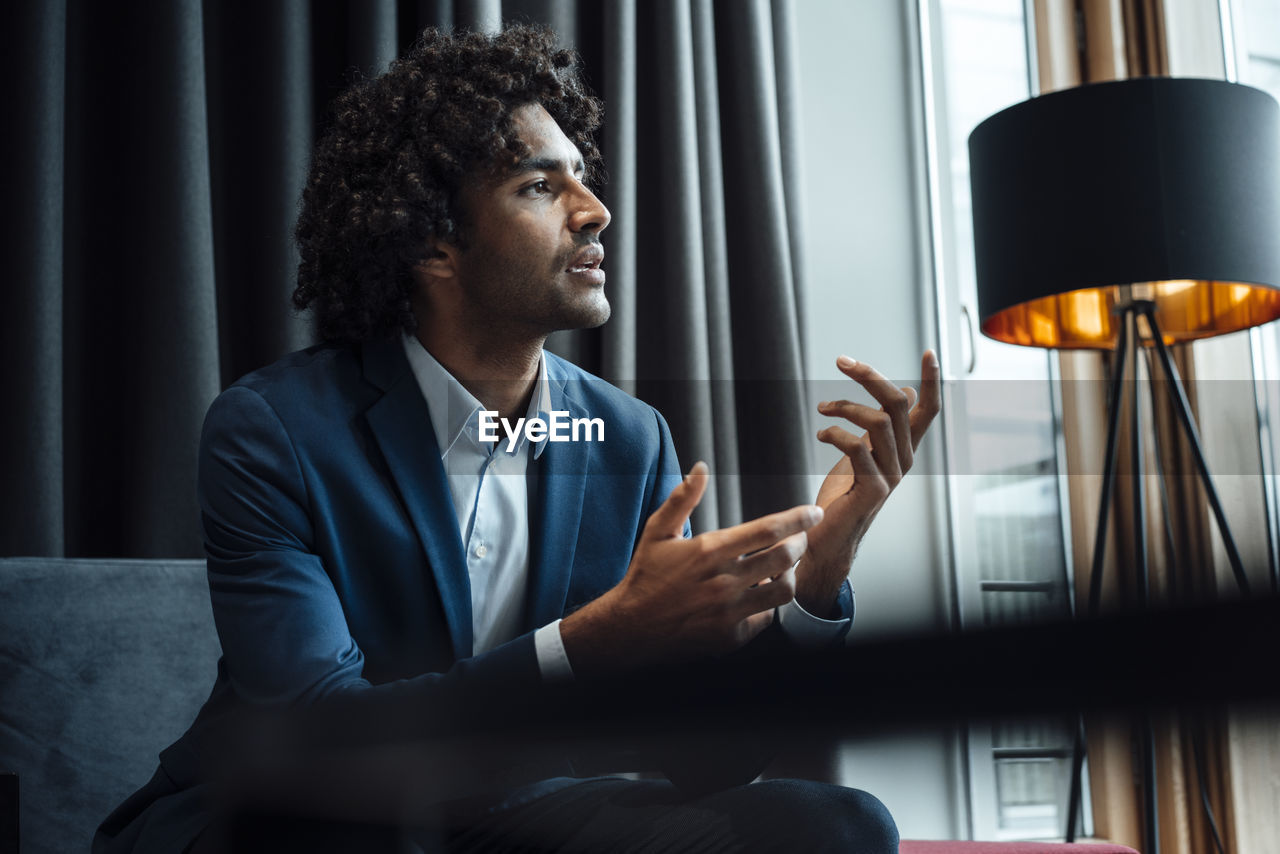 MAN LOOKING AT CAMERA WHILE SITTING IN OFFICE