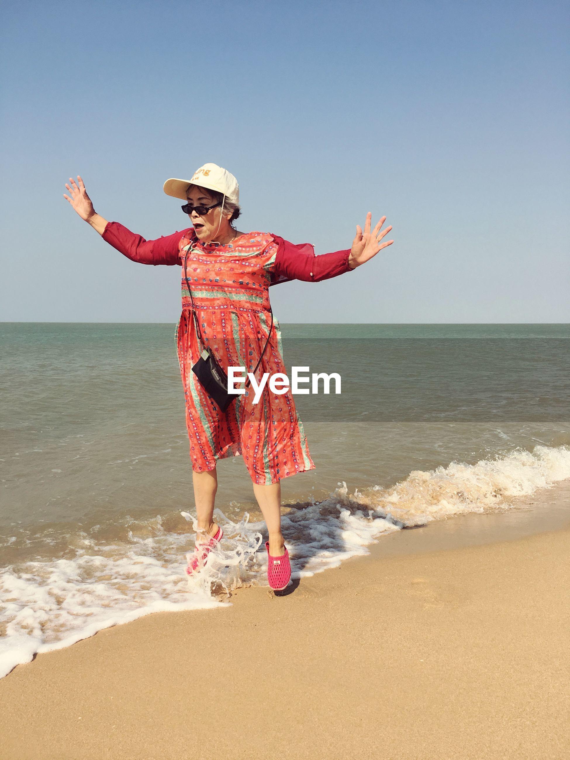 Senior woman jumping at beach against sky