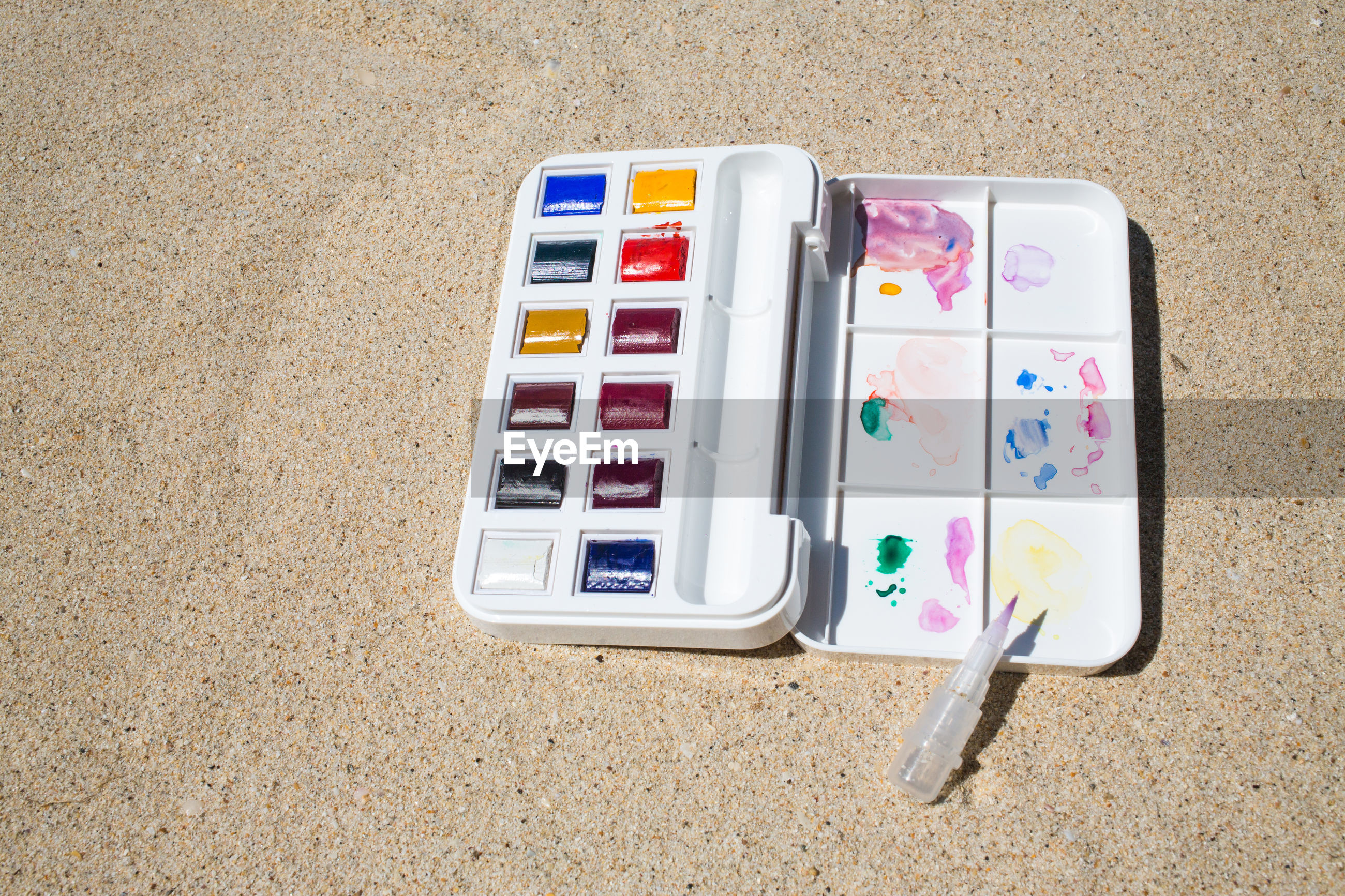 High angle view of multi colored watercolor paints on sand