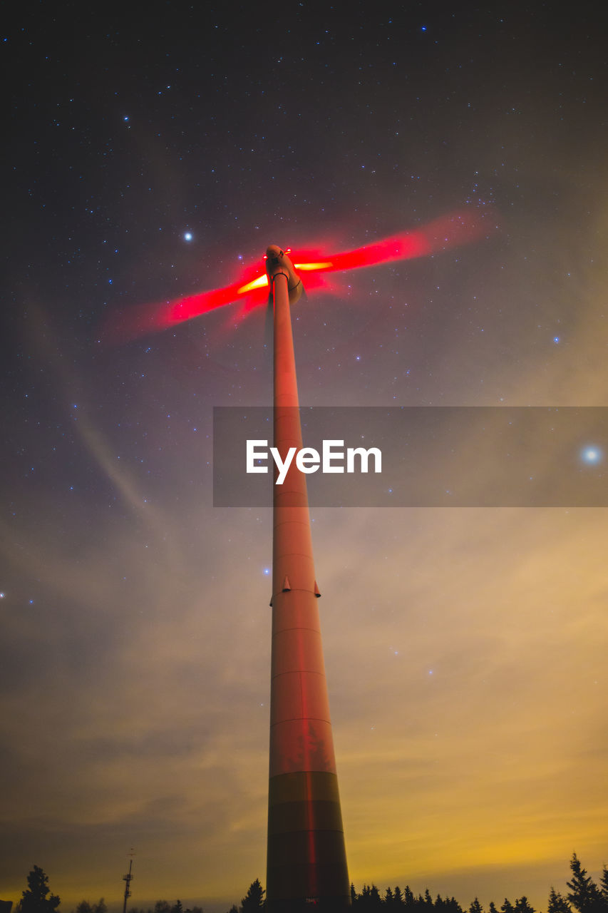 LOW ANGLE VIEW OF WIND TURBINES AT NIGHT