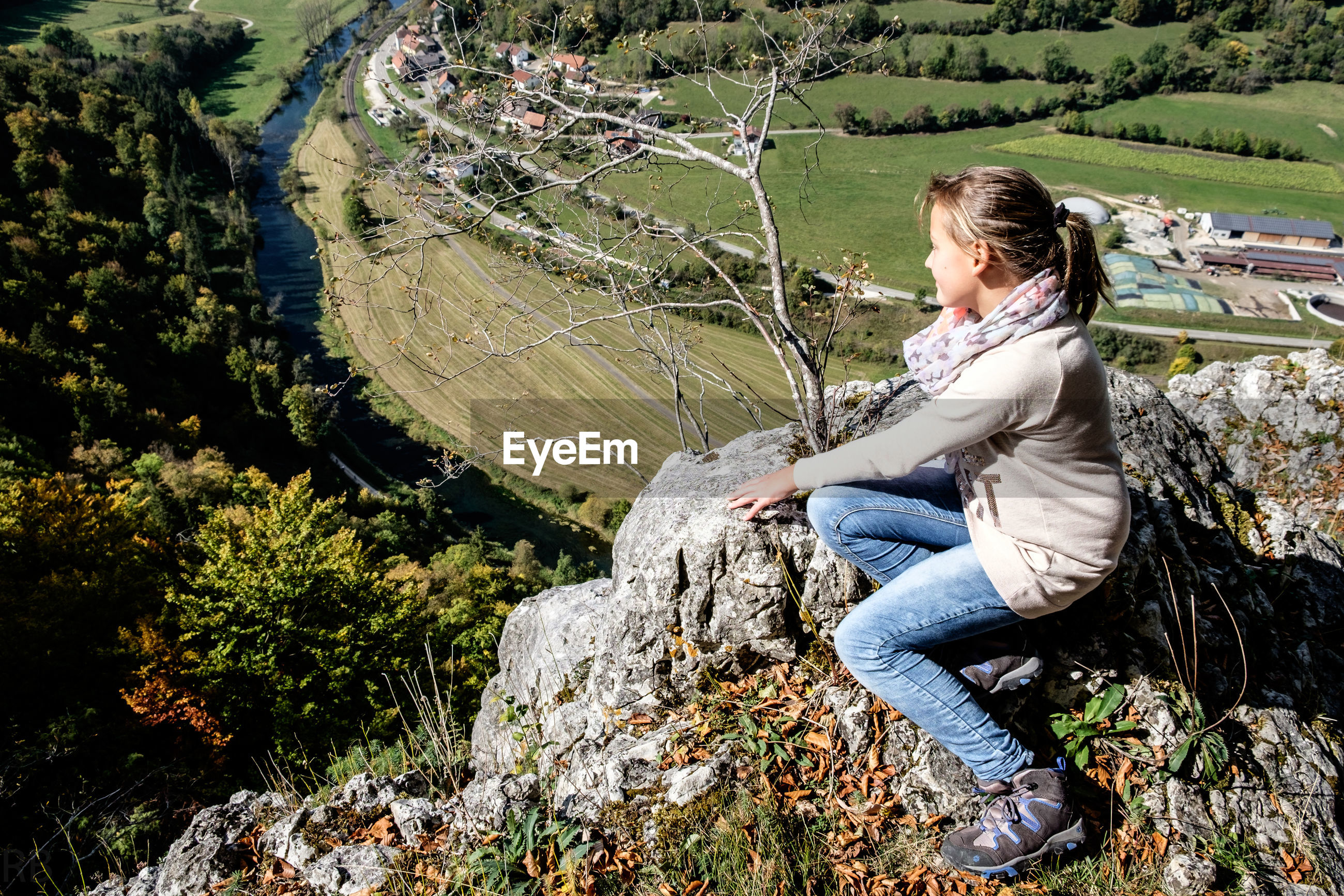 High angle view of woman sitting on cliff