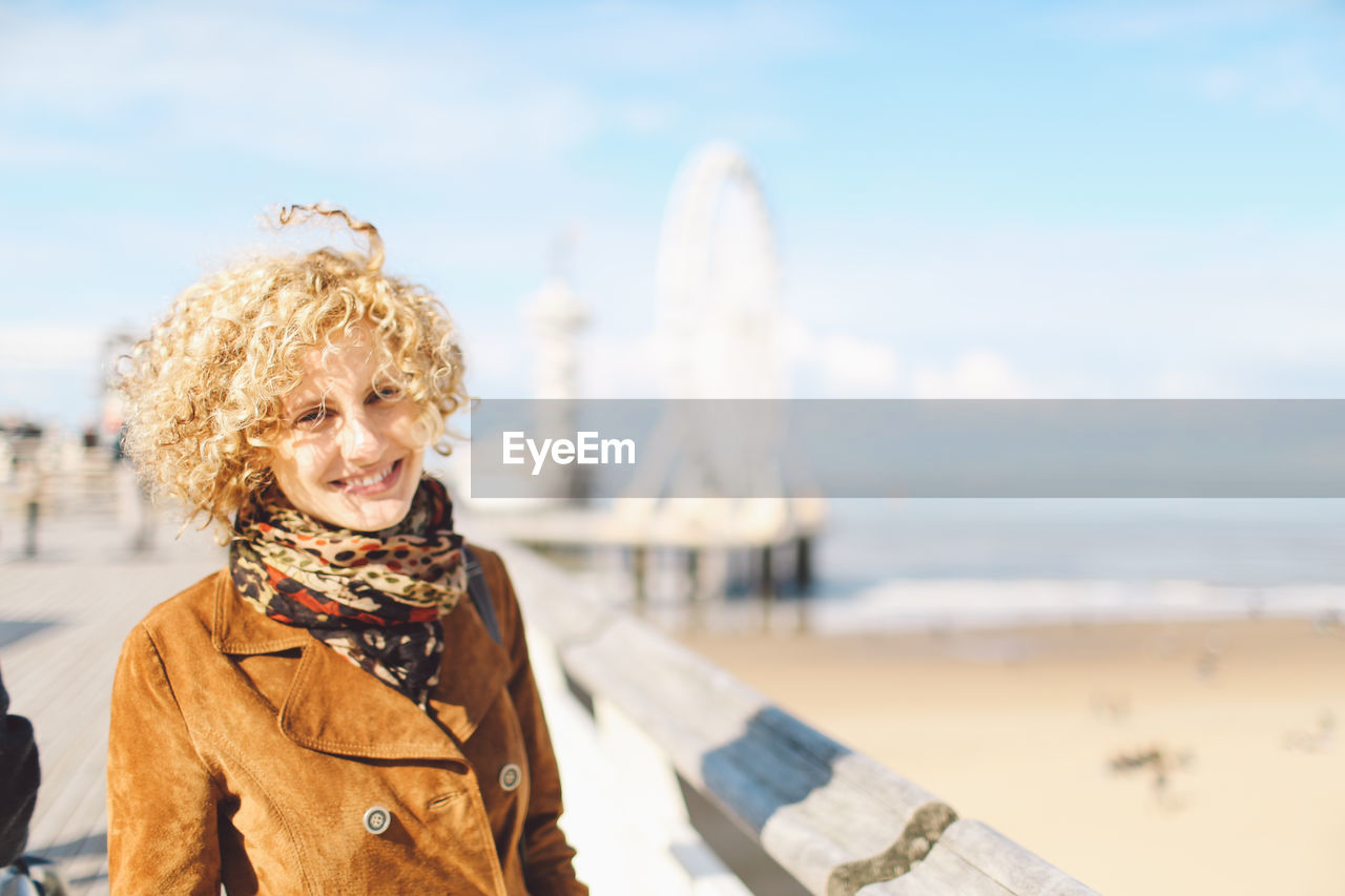 Portrait Of Smiling Woman Standing By Beach