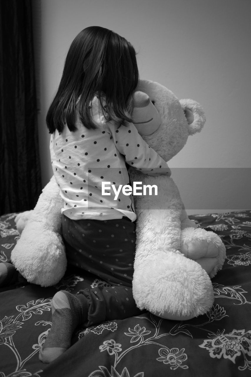Rear View Of Girl Playing With Teddy Bear On Bed At Home