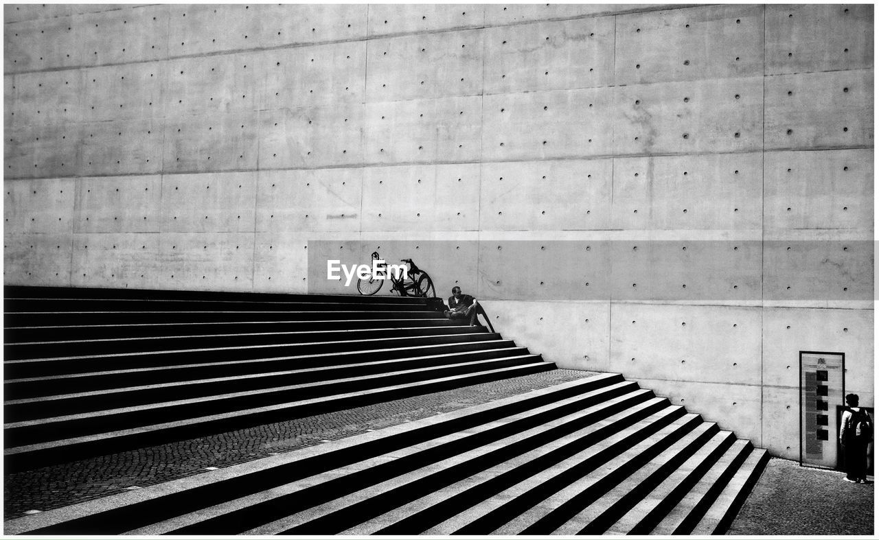 Man By Bicycle Sitting On Steps Against Wall