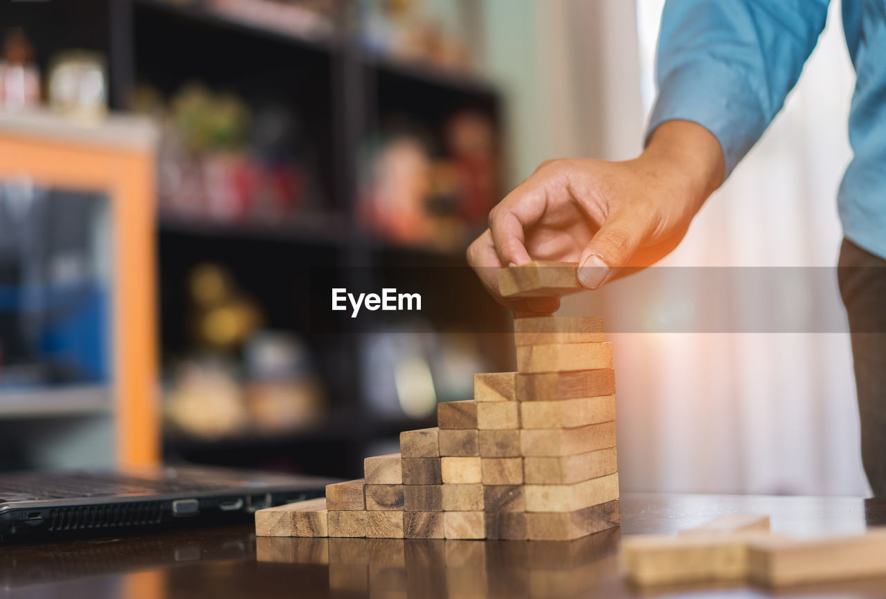 Midsection Of Businessman Stacking Toy Blocks On Table