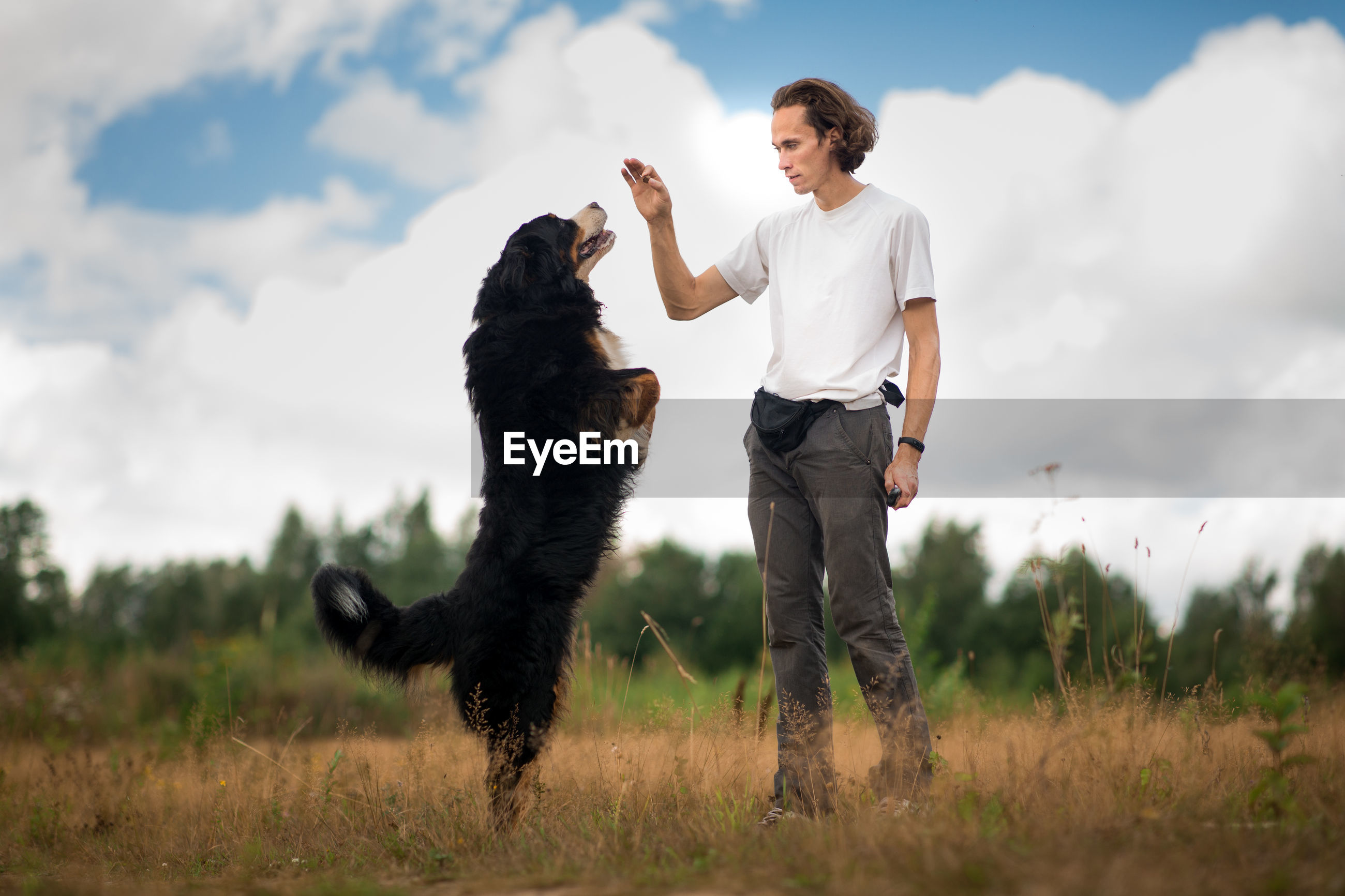 Full length of man with dog standing on field
