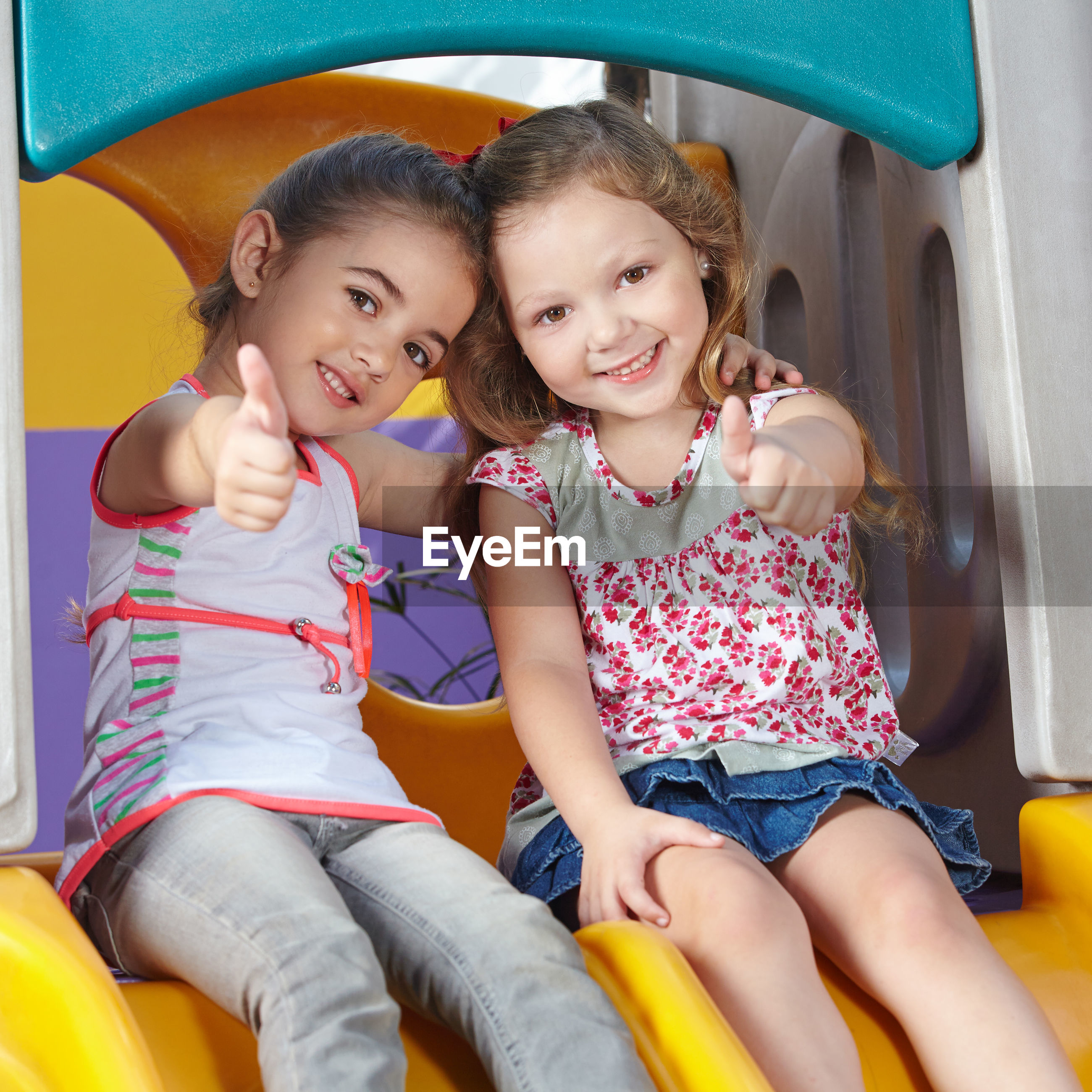 Portrait of friends showing thumbs up while sitting on slide outdoors