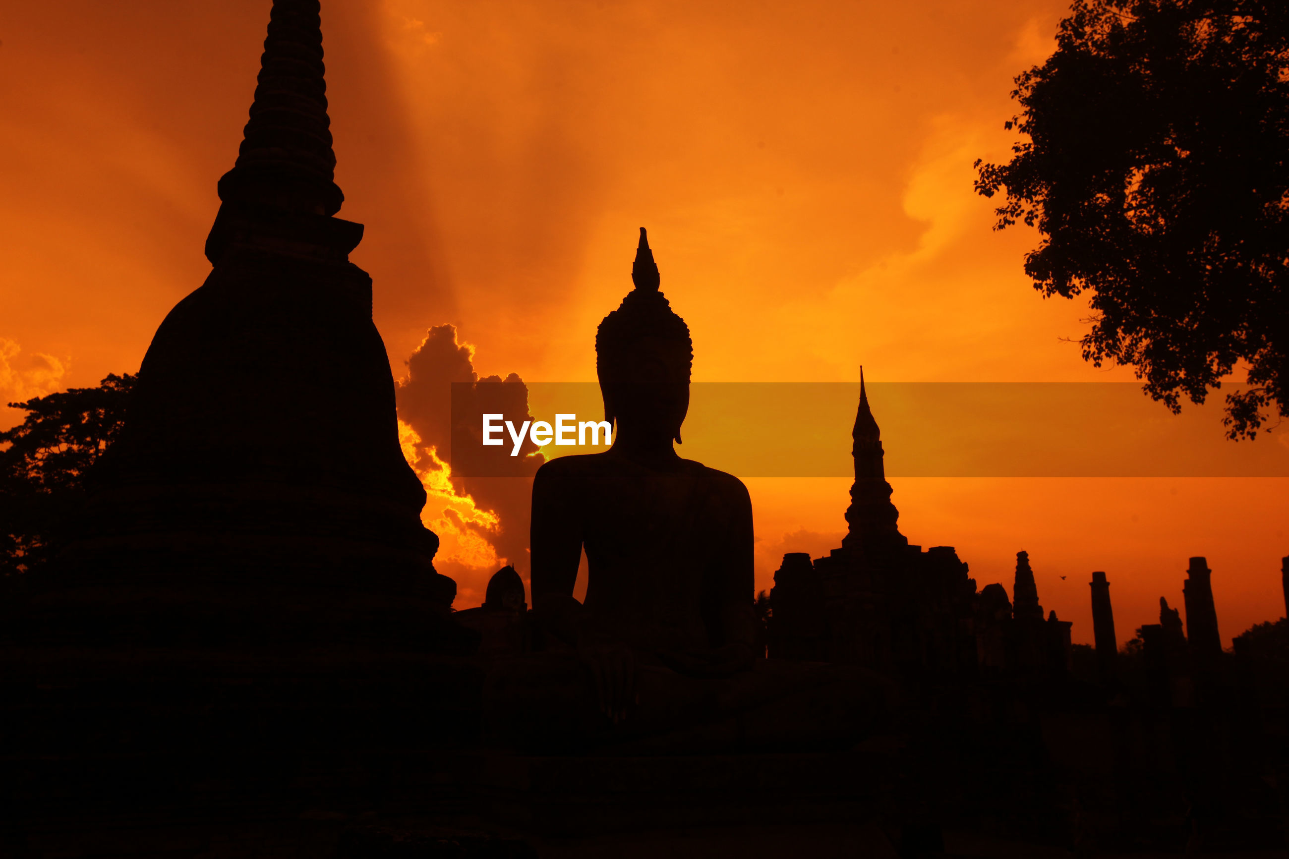 Silhouette buddhist temple against dramatic sky at sunset