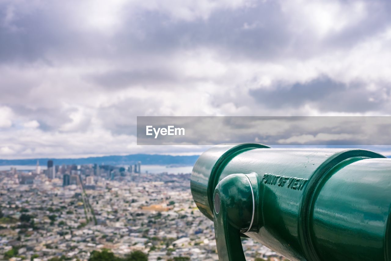 Close-Up Of Telescope With City Buildings In Background