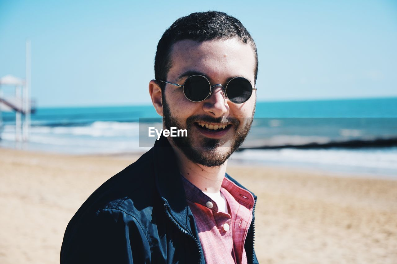 Close-Up Portrait Of Bearded Young Man Wearing Sunglasses During Sunny Day