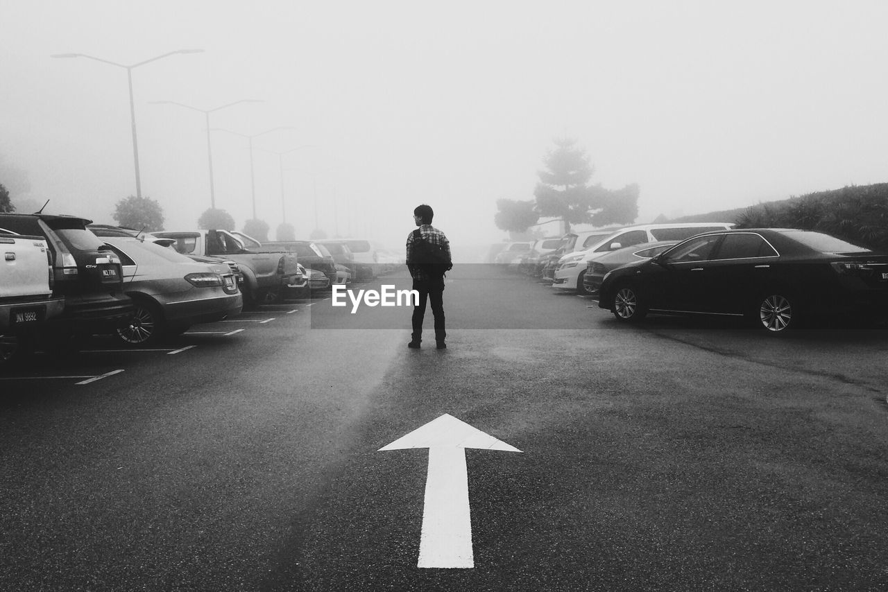 Rear View Of Man Standing By Arrow Symbol Amidst Cars During Foggy Weather