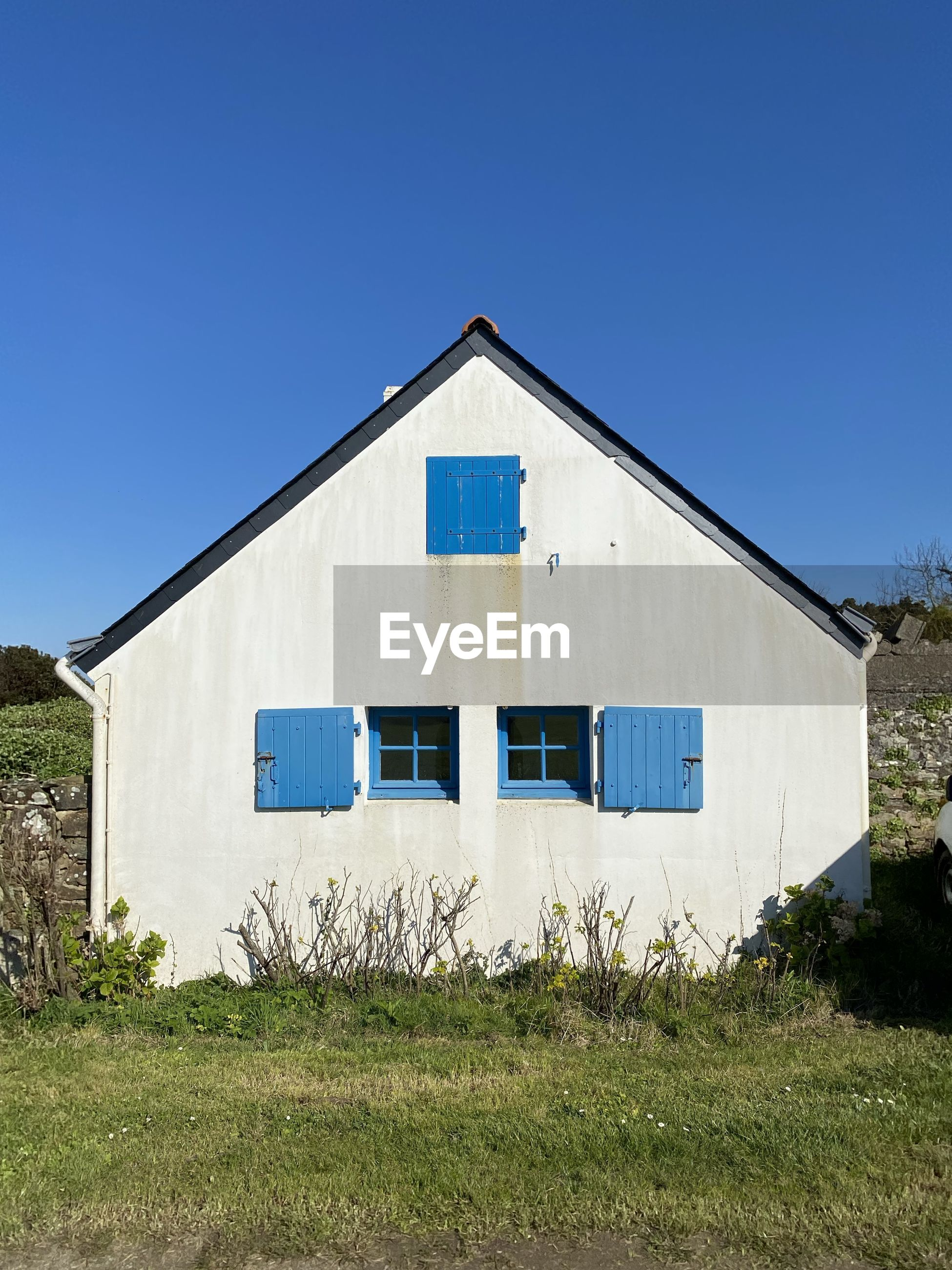 EXTERIOR OF HOUSE ON FIELD AGAINST CLEAR SKY