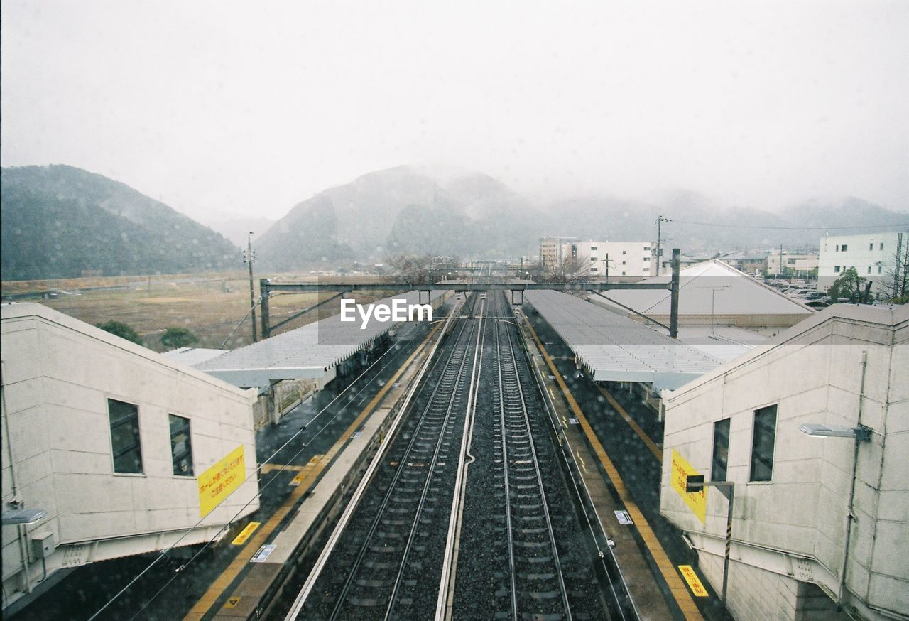 transportation, railroad track, mountain, rail transportation, sky, track, built structure, architecture, nature, day, mode of transportation, building exterior, no people, high angle view, outdoors, fog, public transportation, city, long
