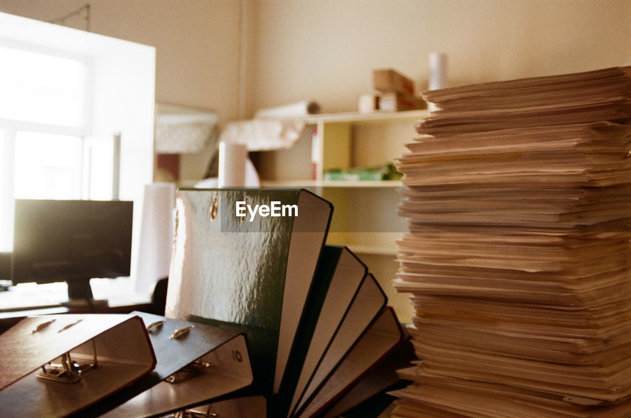 indoors, still life, stack, table, large group of objects, book, education, publication, no people, furniture, focus on foreground, office, paper, close-up, shelf, desk, wood - material, business, home interior, literature, paperwork