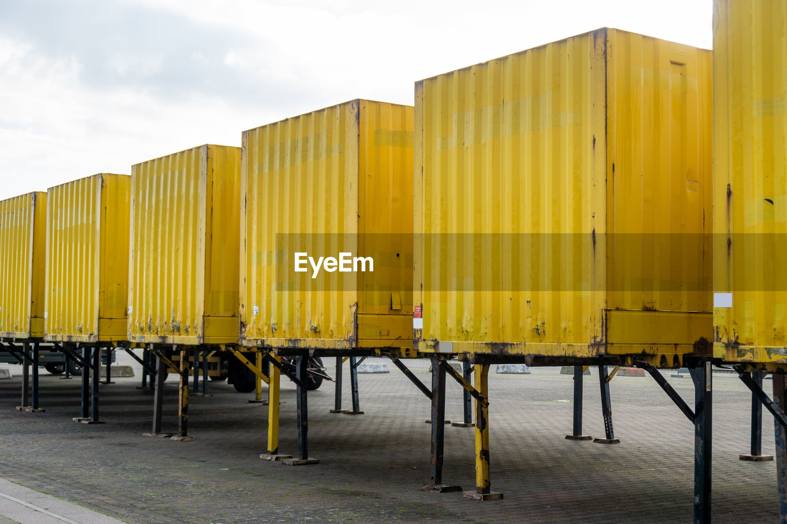 YELLOW METALLIC STRUCTURE ON PIER AGAINST SKY IN CITY