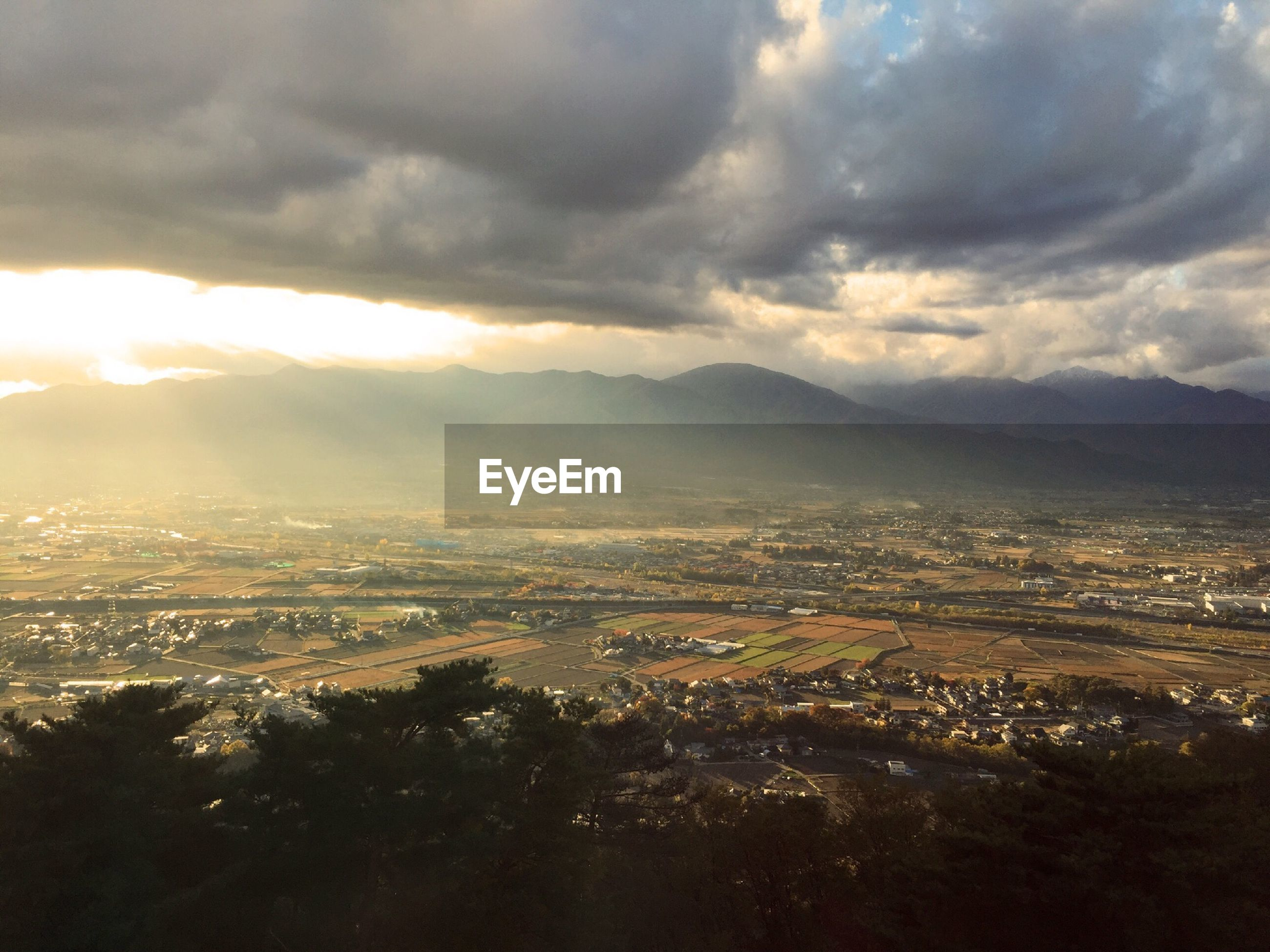 Aerial view of landscape against mountains with cloudy sky