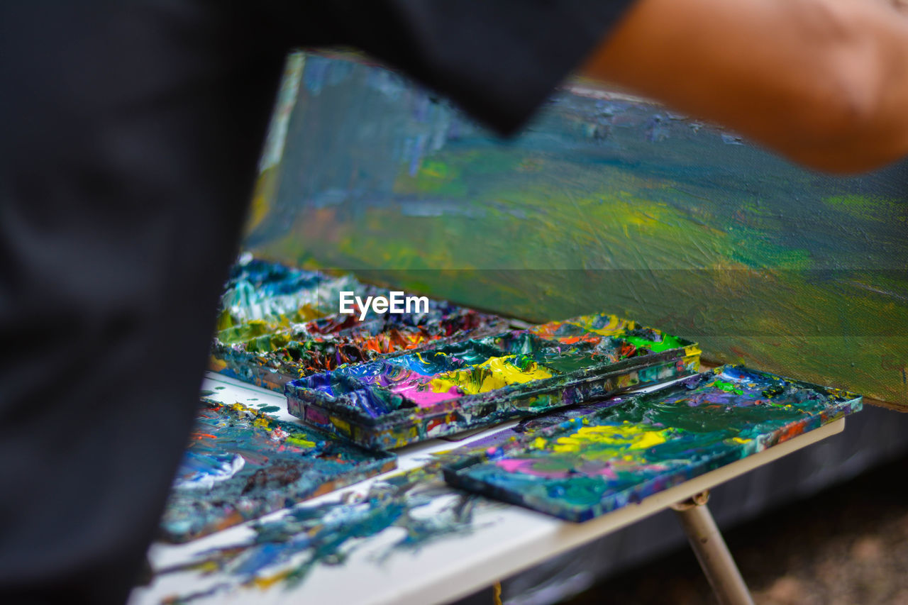 art and craft, multi colored, selective focus, craft, palette, hand, brush, human hand, one person, creativity, paintbrush, indoors, unrecognizable person, occupation, skill, human body part, art and craft equipment, paint, close-up, real people, messy, finger