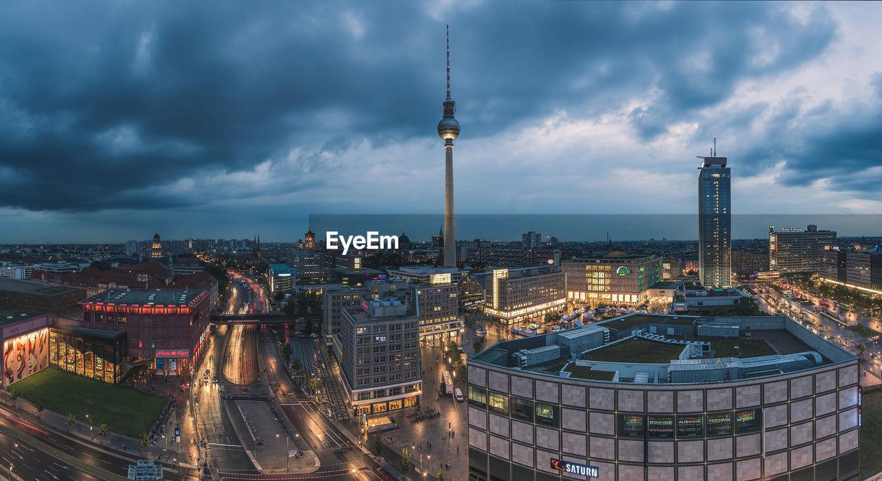 Fernsehturm In Illuminated Cityscape Against Cloudy Sky At Dusk