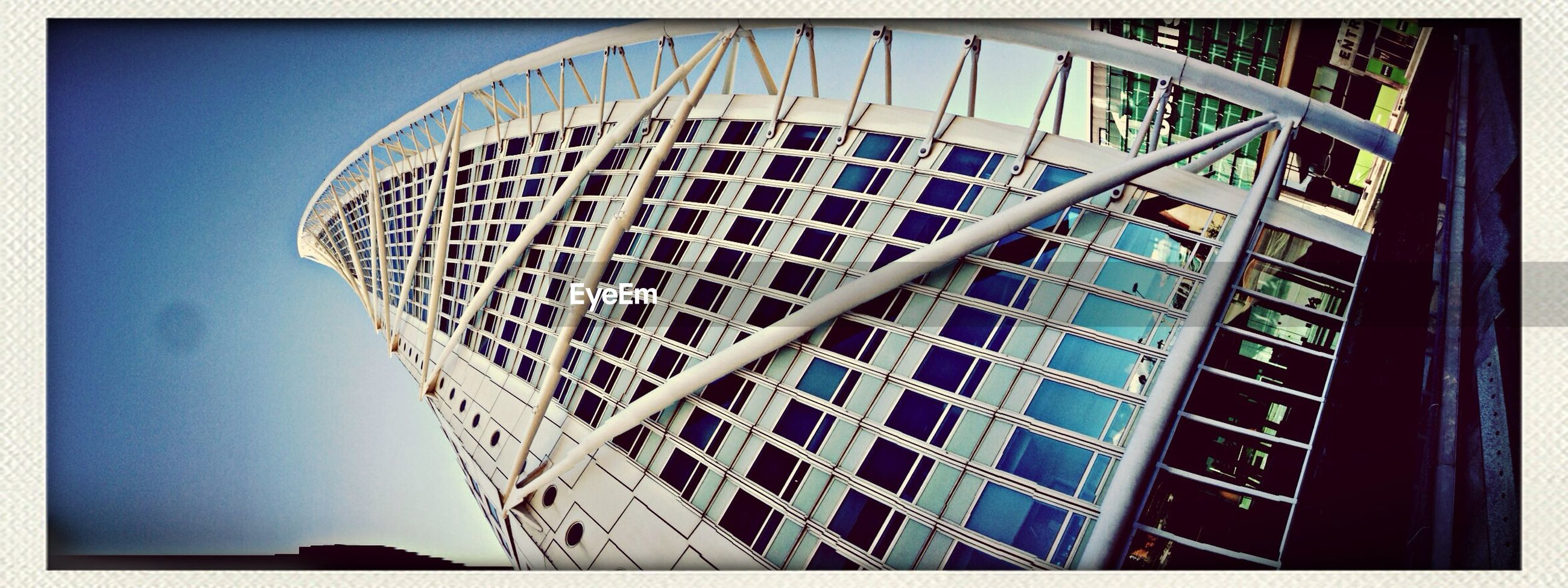 low angle view, transfer print, architecture, built structure, building exterior, auto post production filter, modern, clear sky, pattern, tower, tall - high, glass - material, building, day, city, office building, sky, blue, no people, outdoors