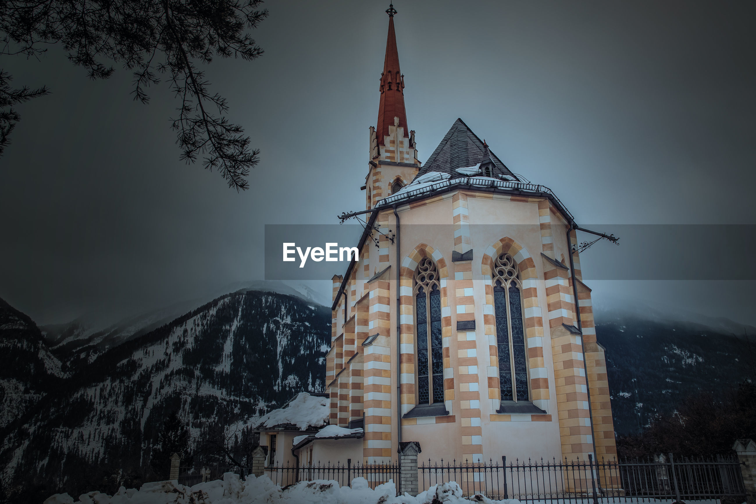 religion, spirituality, place of worship, architecture, snow, weather, cold temperature, built structure, building exterior, no people, winter, low angle view, outdoors, sky, nature, tree, mountain, day, travel destinations, fog