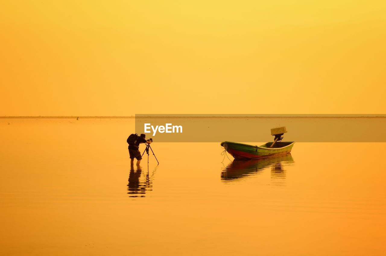 Man Photographing Boat Moored In Sea Against Clear Sky During Sunset