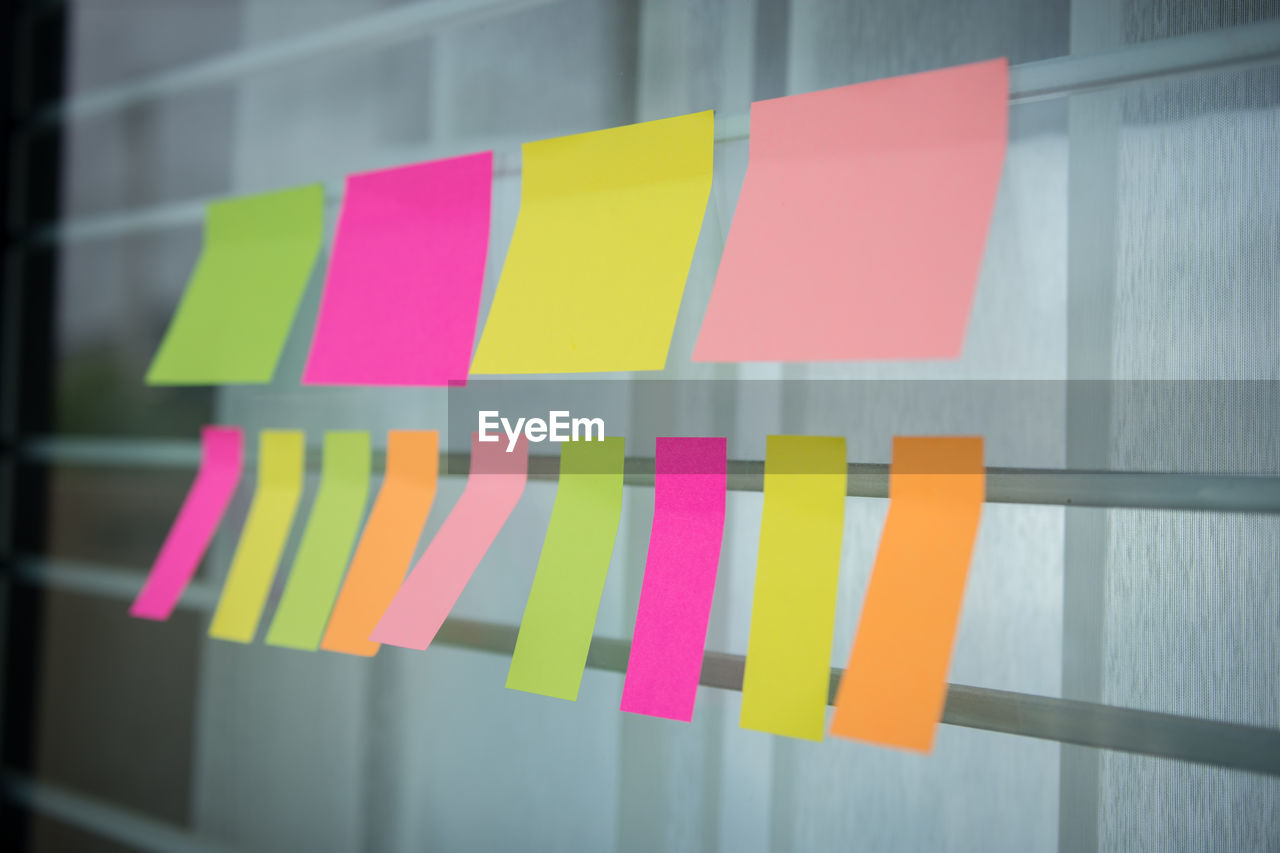 Close-up of blank adhesive notes hanging against window