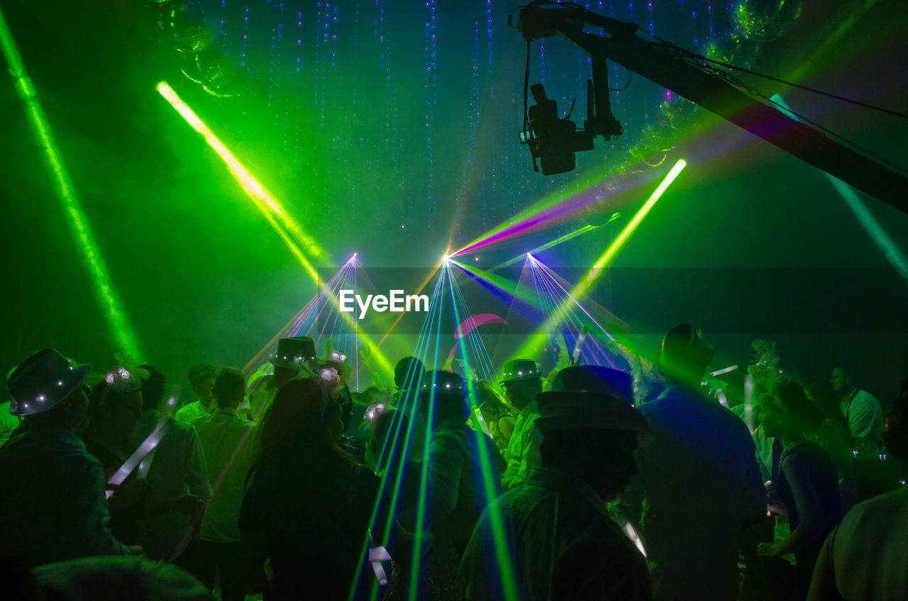 Green Light Beams Falling On People In Nightclub