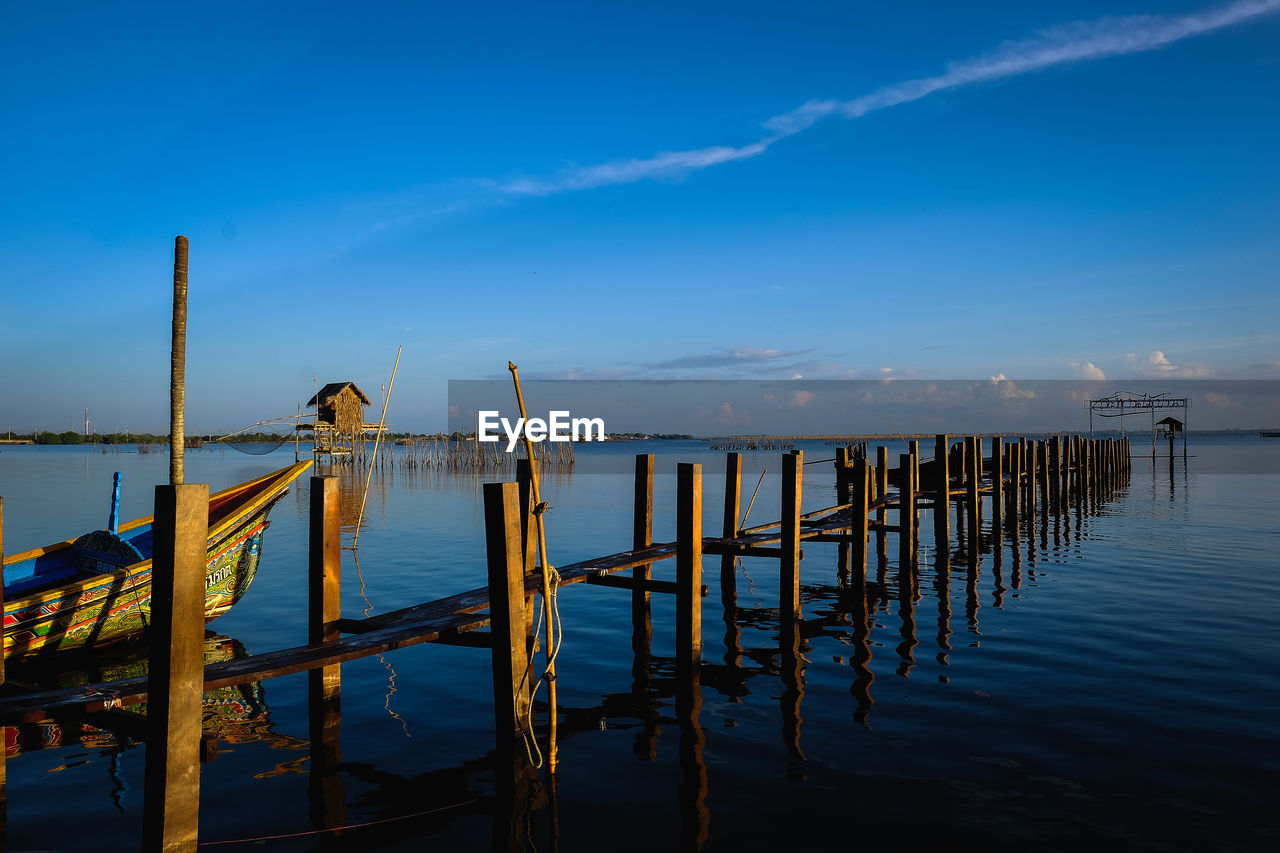WOODEN POSTS ON PIER AGAINST SKY