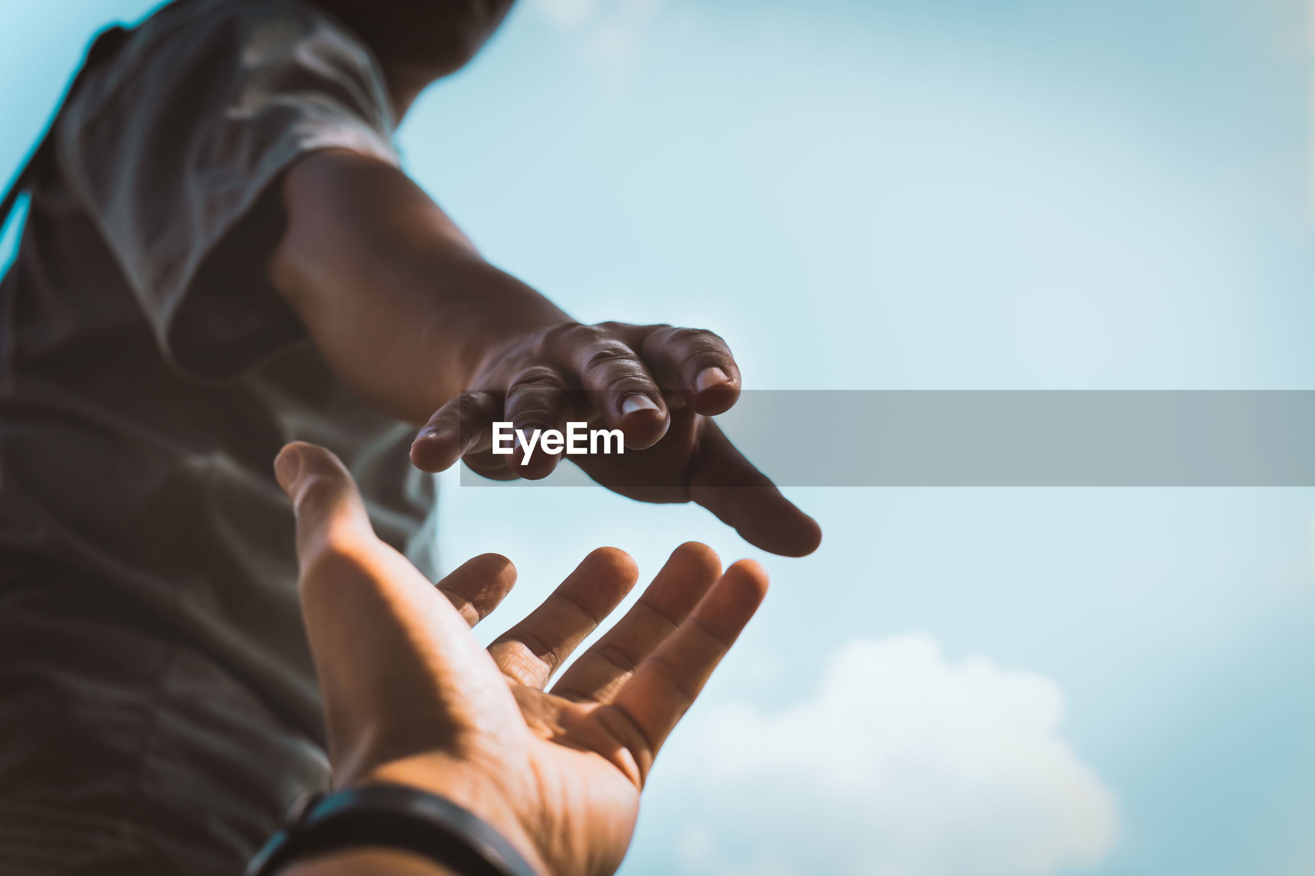 Cropped image of man reaching towards girlfriend hand against sky