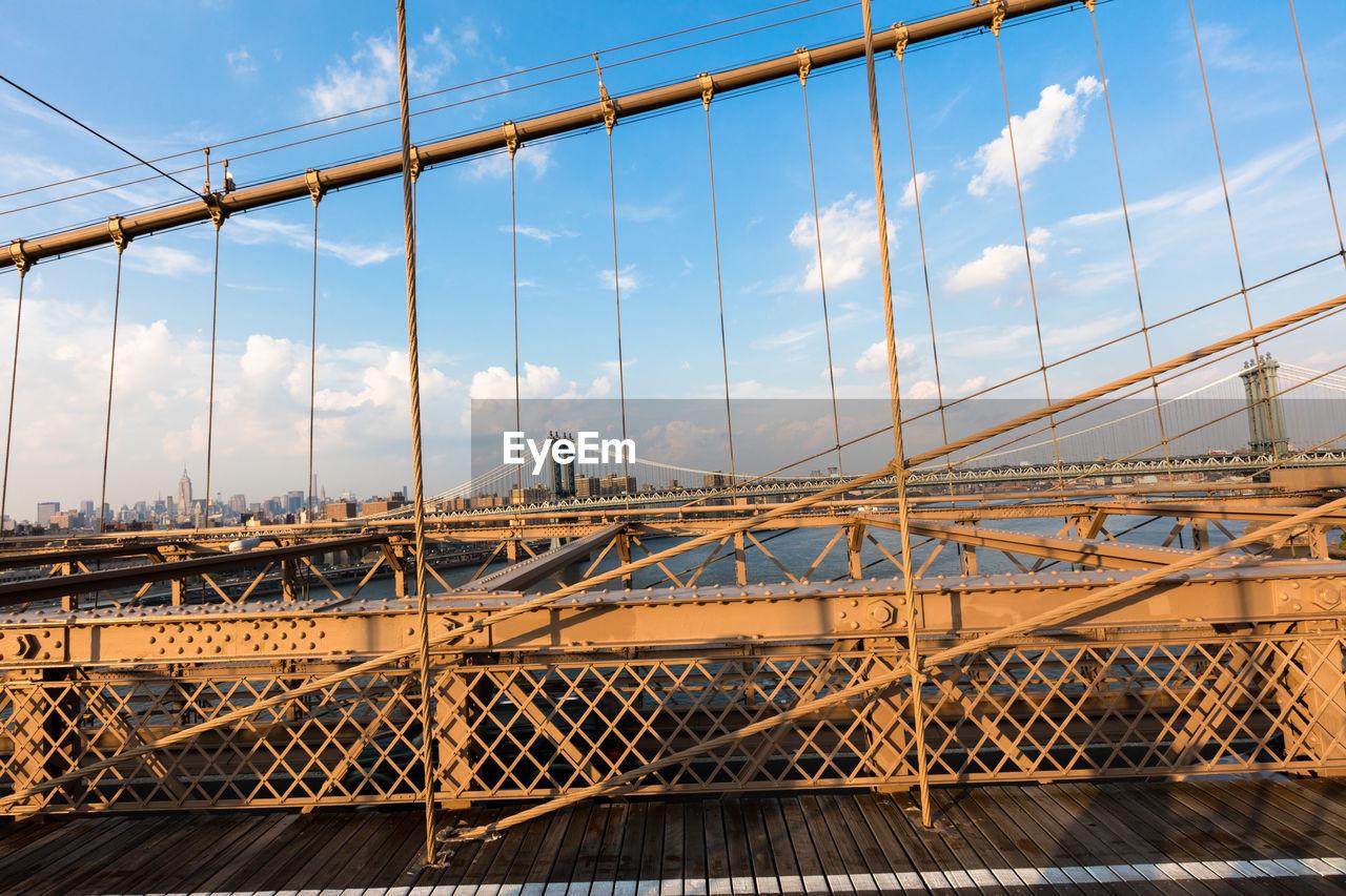 bridge - man made structure, connection, built structure, architecture, sky, transportation, city, suspension bridge, cloud - sky, no people, outdoors, day, bridge, building exterior, cityscape